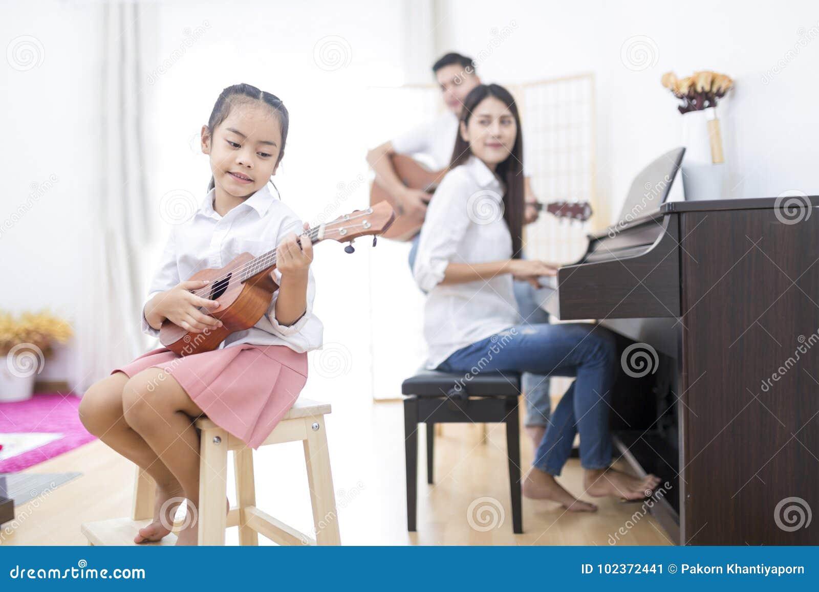Ασιατική οικογένεια, κόρη που παίζει ukulele, κιθάρα παιχνιδιού πατέρων, σκώρος