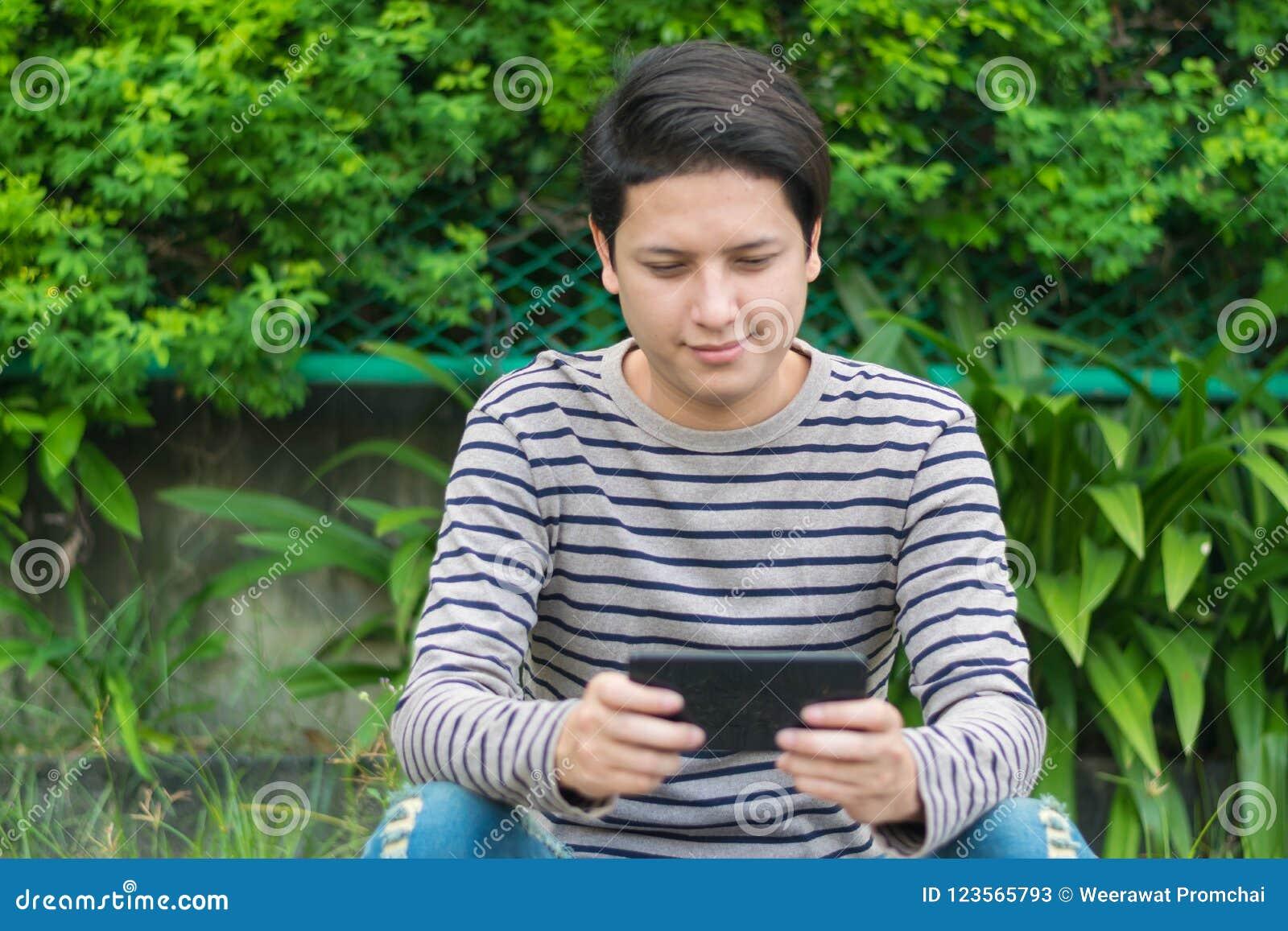 Ασιατική συνεδρίαση ατόμων και χρησιμοποίηση του smartphone