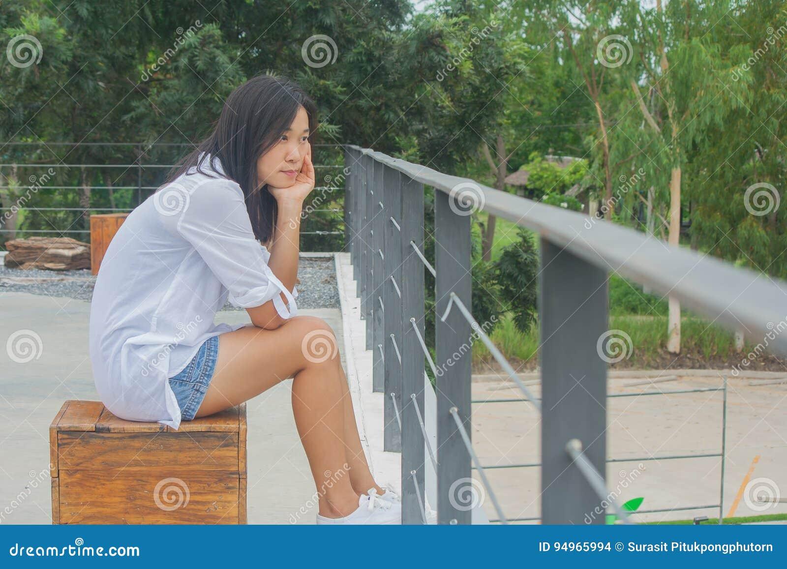 Ασιατική συνεδρίαση γυναικών στην ξύλινη καρέκλα σε επίπεδης κορυφής των κτηρίων στεγών, χαλαρώνοντας και κοιτάζοντας προς τα εμπ
