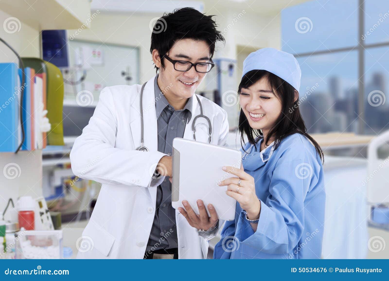 Ασιατικοί γιατροί με την ταμπλέτα στην κλινική