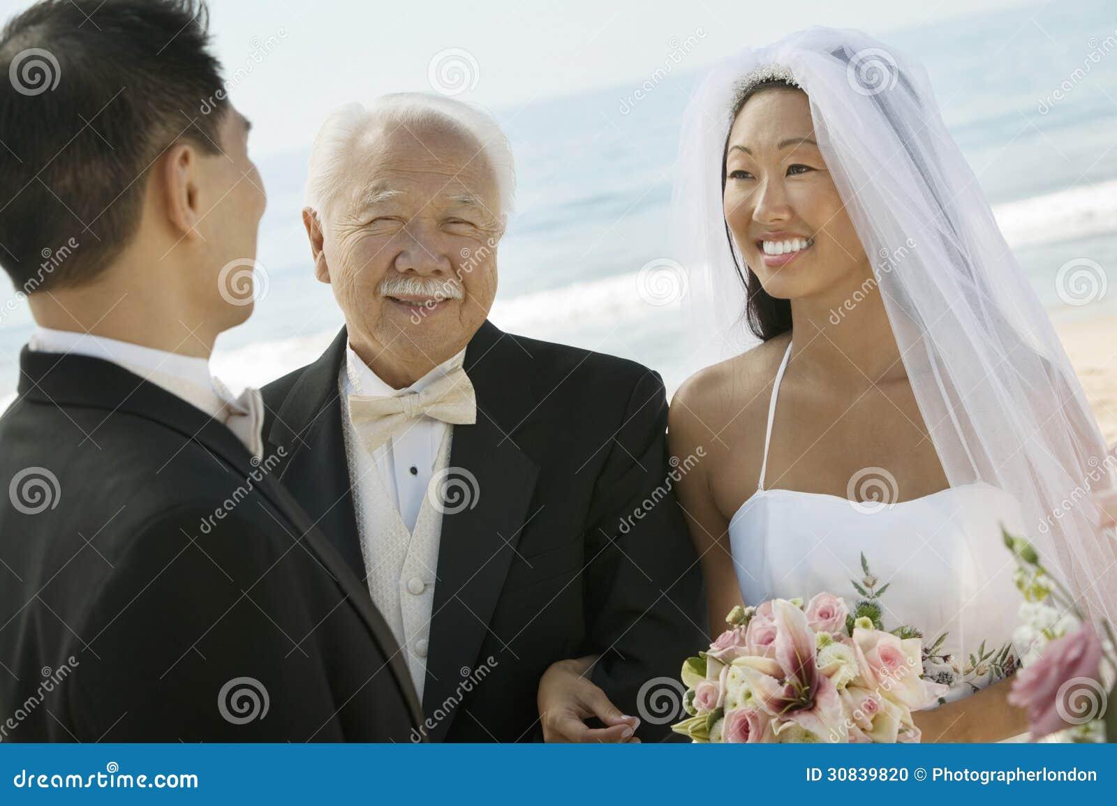 Ασιατικοί νύφη και νεόνυμφος με τον πατέρα