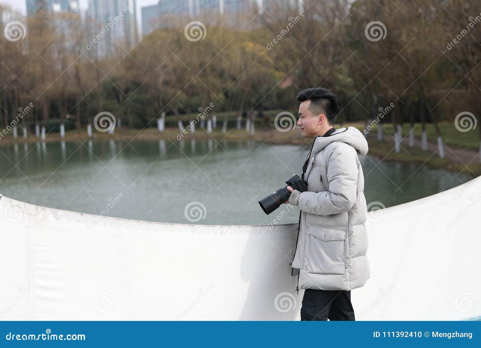 Ασιατικός κινεζικός φωτογράφος ατόμων στο πάρκο