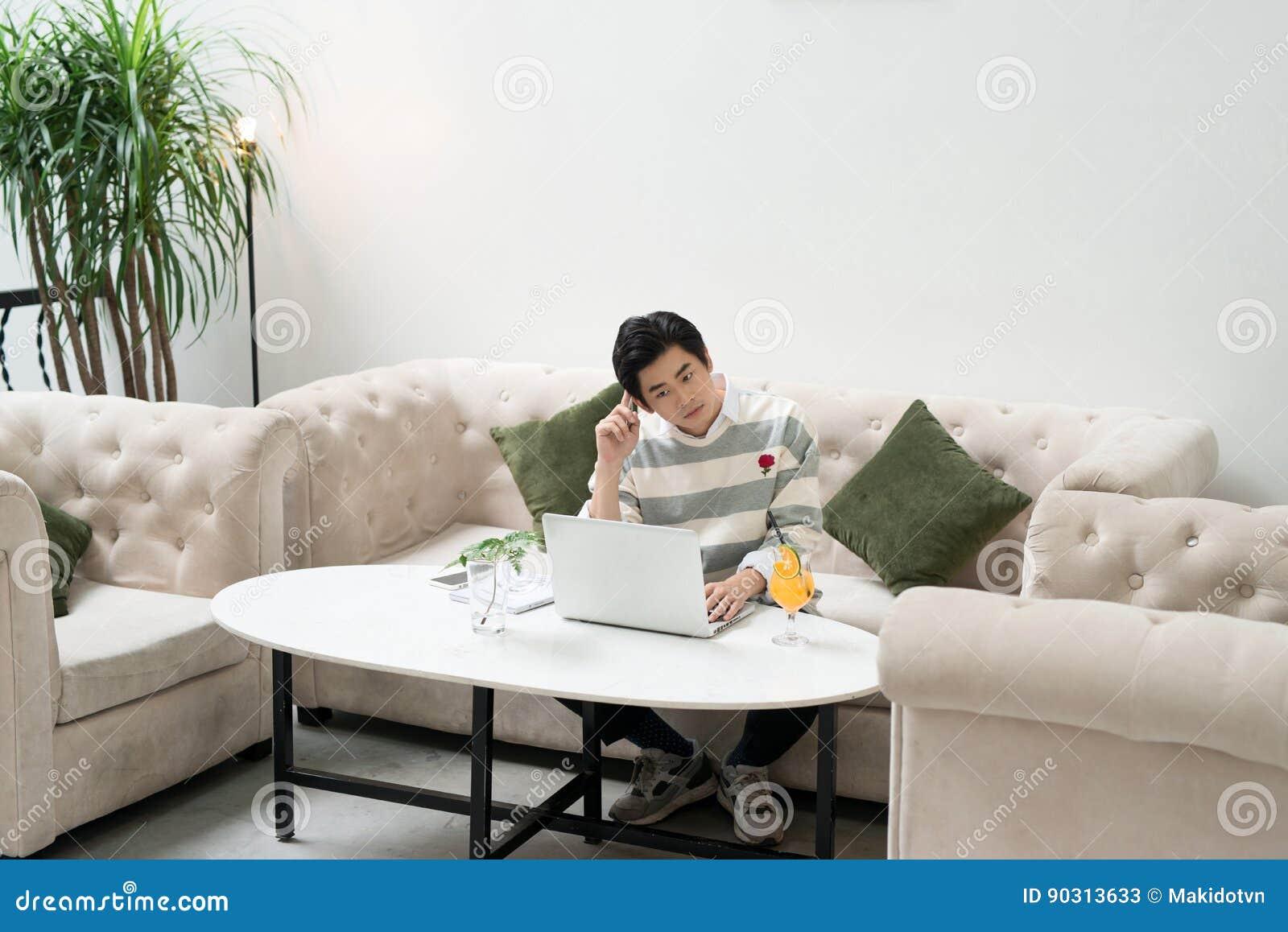 Ασιατικός νέος επιχειρηματίας που εργάζεται στο lap-top του σε μια καφετερία