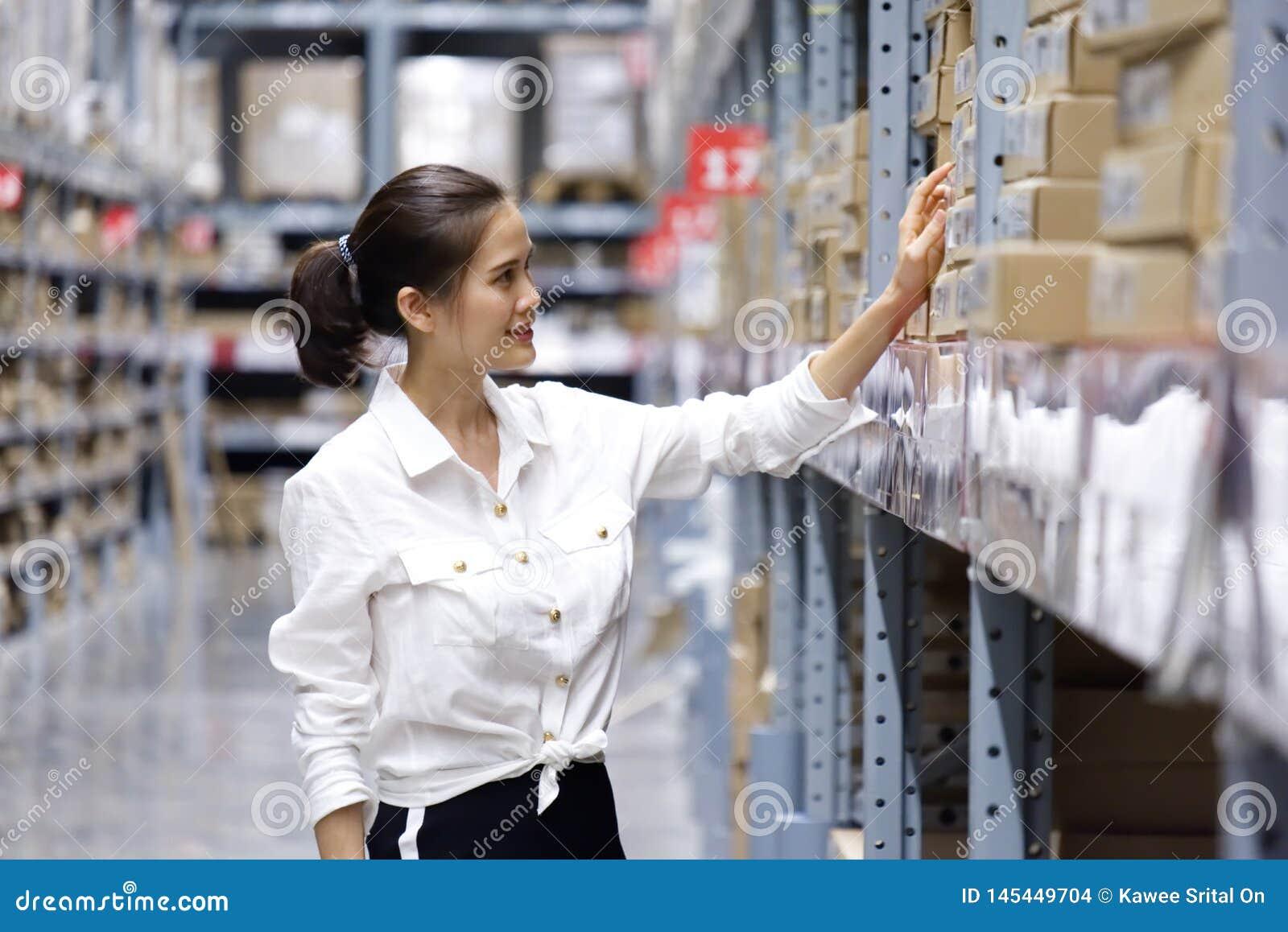 Ασιατικός όμορφος πελάτης που ψάχνει τα προϊόντα στην αποθήκη εμπορευμάτων καταστημάτων Το κορίτσι που χρησιμοποιεί το σημείο χερ
