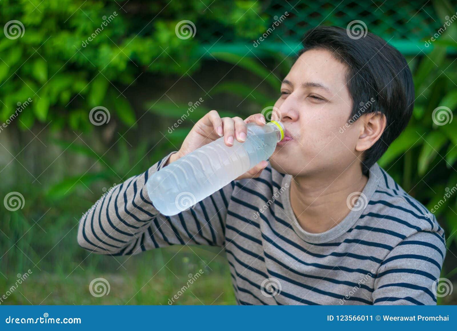 Ασιατικό άτομο που κάθεται και που πίνει ένα μπουκάλι νερό