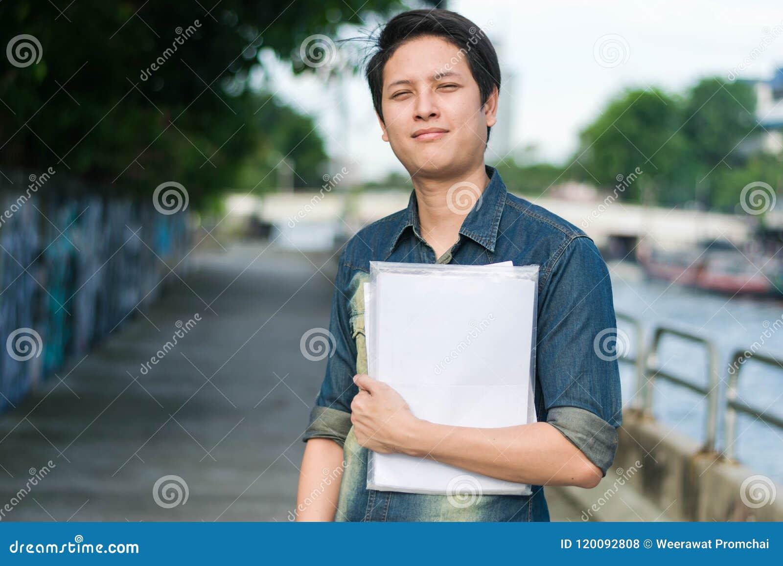 Ασιατικό άτομο που στέκεται και που κρατά το αρχείο εγγράφων