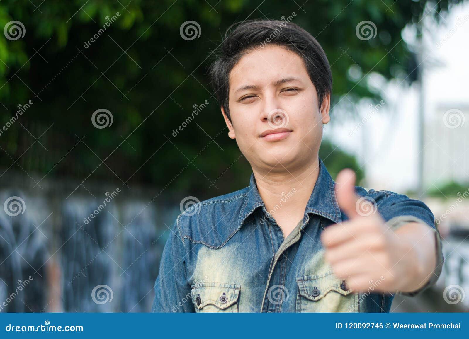 Ασιατικό άτομο που στέκεται και που παρουσιάζει αντίχειρα