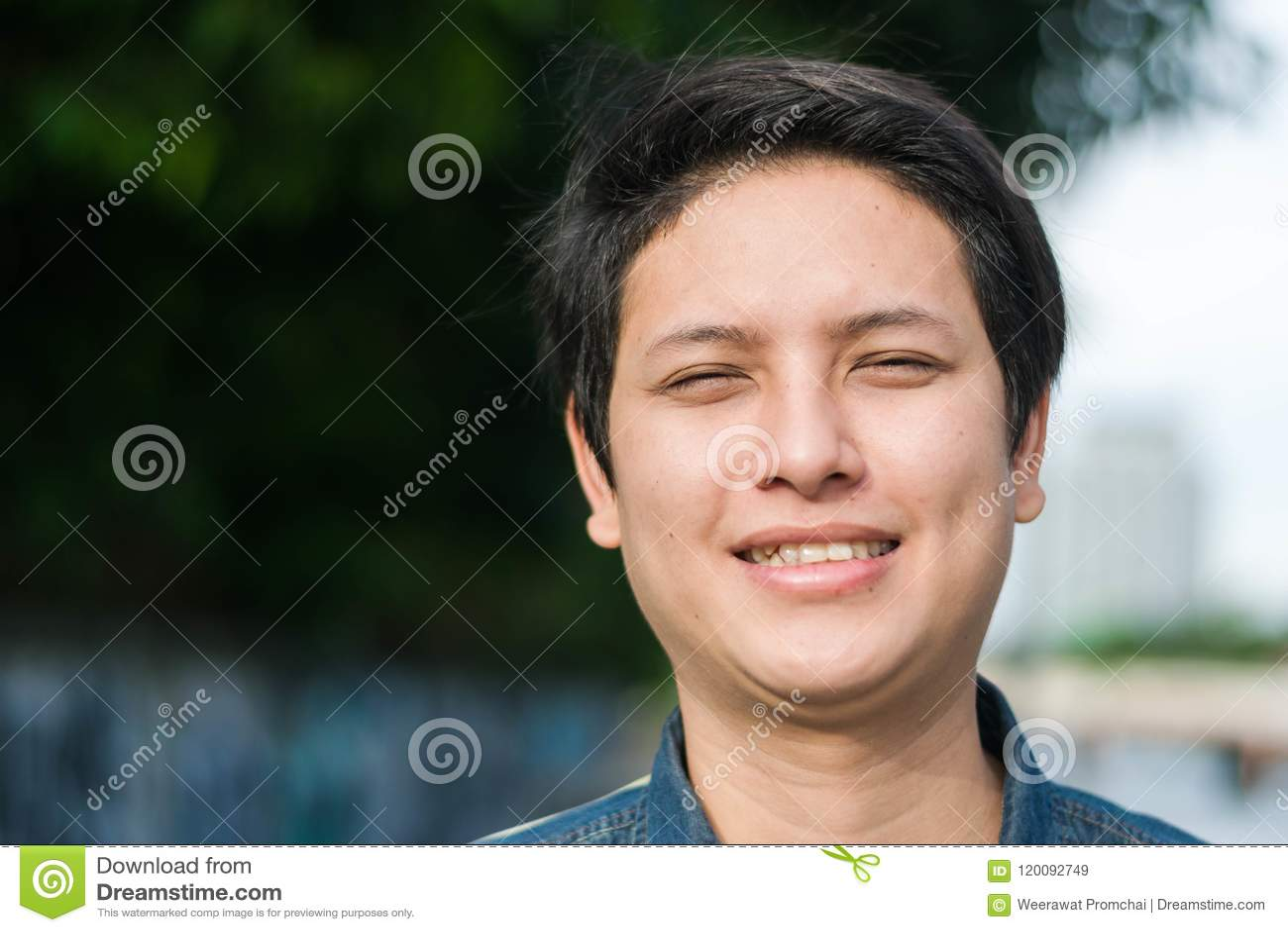 Ασιατικό άτομο που στέκεται και που παρουσιάζει ευτυχές χαμόγελό του