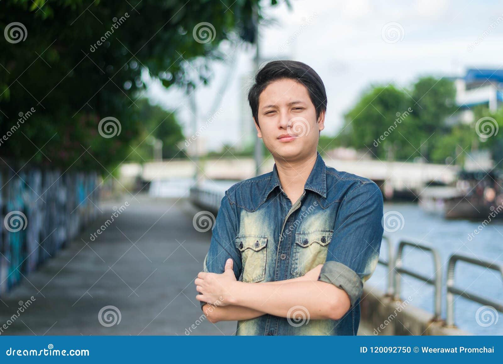 Ασιατικό άτομο που στέκεται και που παρουσιάζει ομαλό πρόσωπό του