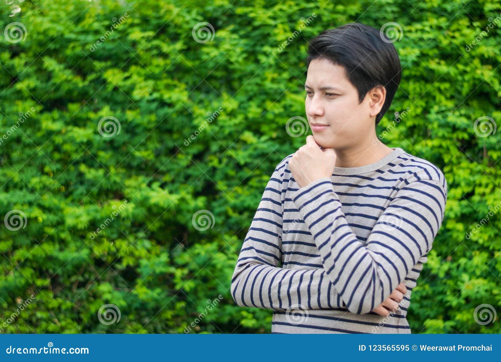 Ασιατικό άτομο που στέκεται και που σκέφτεται κάτι