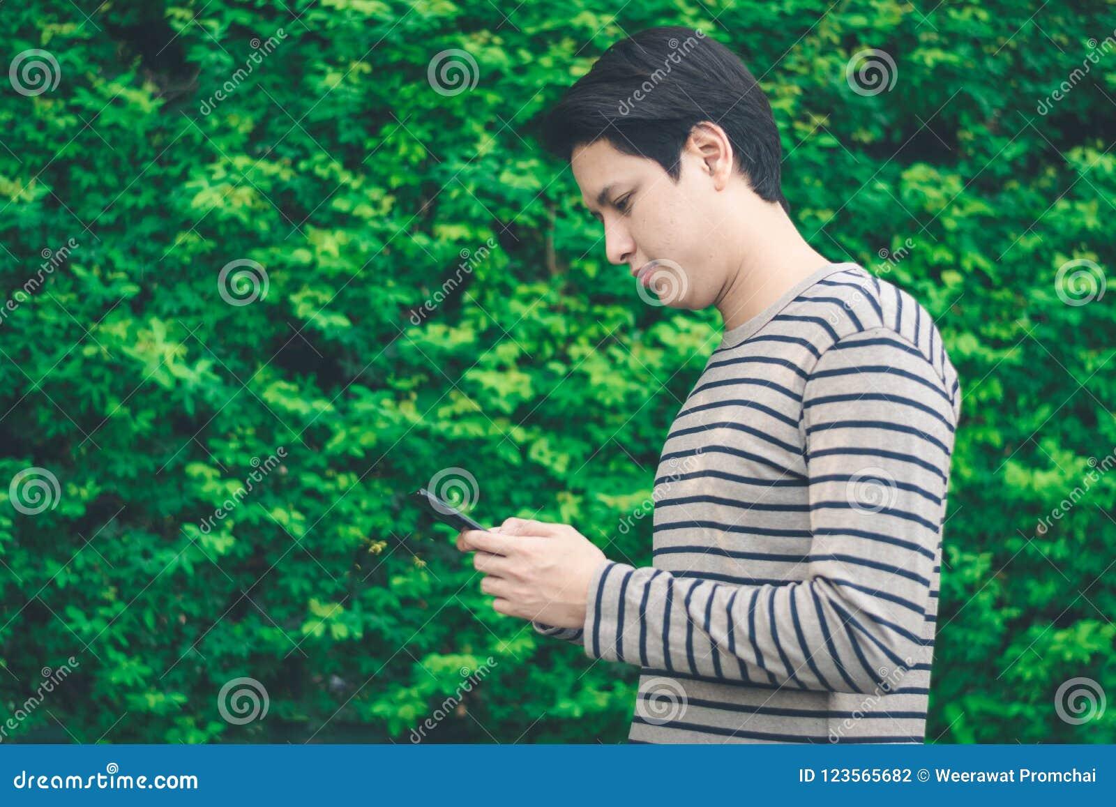 Ασιατικό άτομο που στέκεται και που χρησιμοποιεί το smartphone
