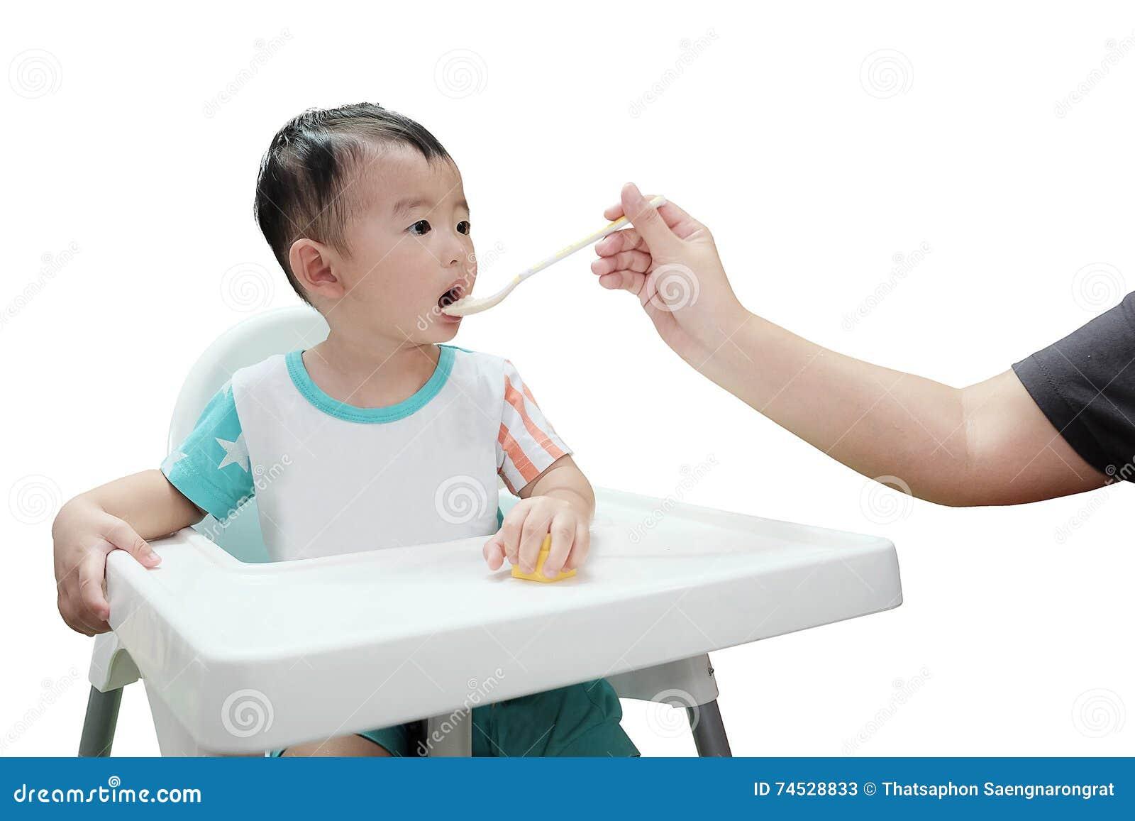 Ασιατικό αγόρι παιδιών που τρώει με το κουτάλι, που απομονώνεται στο άσπρο υπόβαθρο