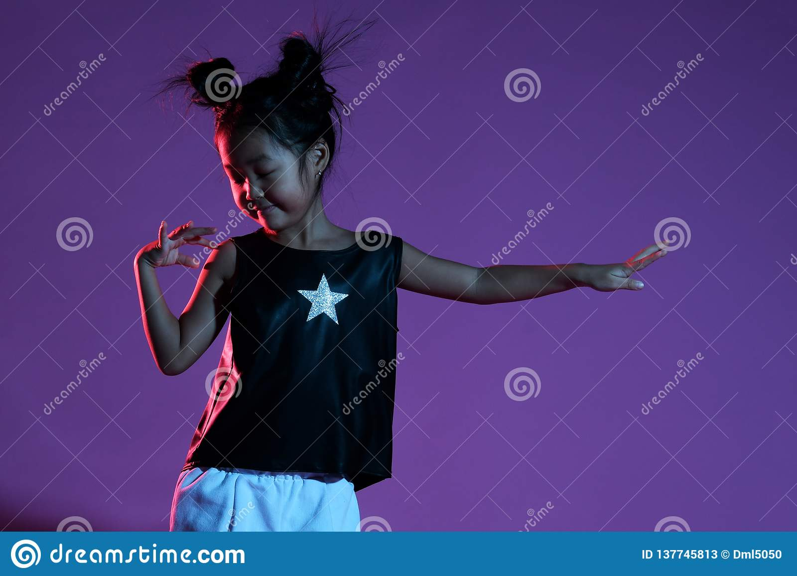 Ασιατικό κορίτσι παιδιών στο πουκάμισο και εσώρουχα με τα αστέρια και τους χορούς