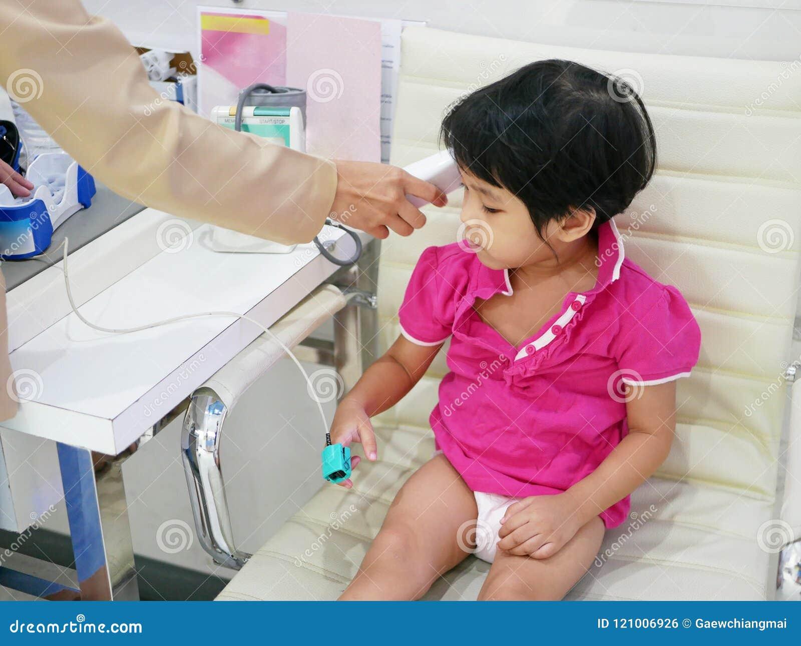 Ασιατικό κοριτσάκι που έχει το ποσό οξυγόνου στο αίμα, το ποσοστό καρδιών, και τη θερμοκρασία της που μετριέται, χρησιμοποιώντας