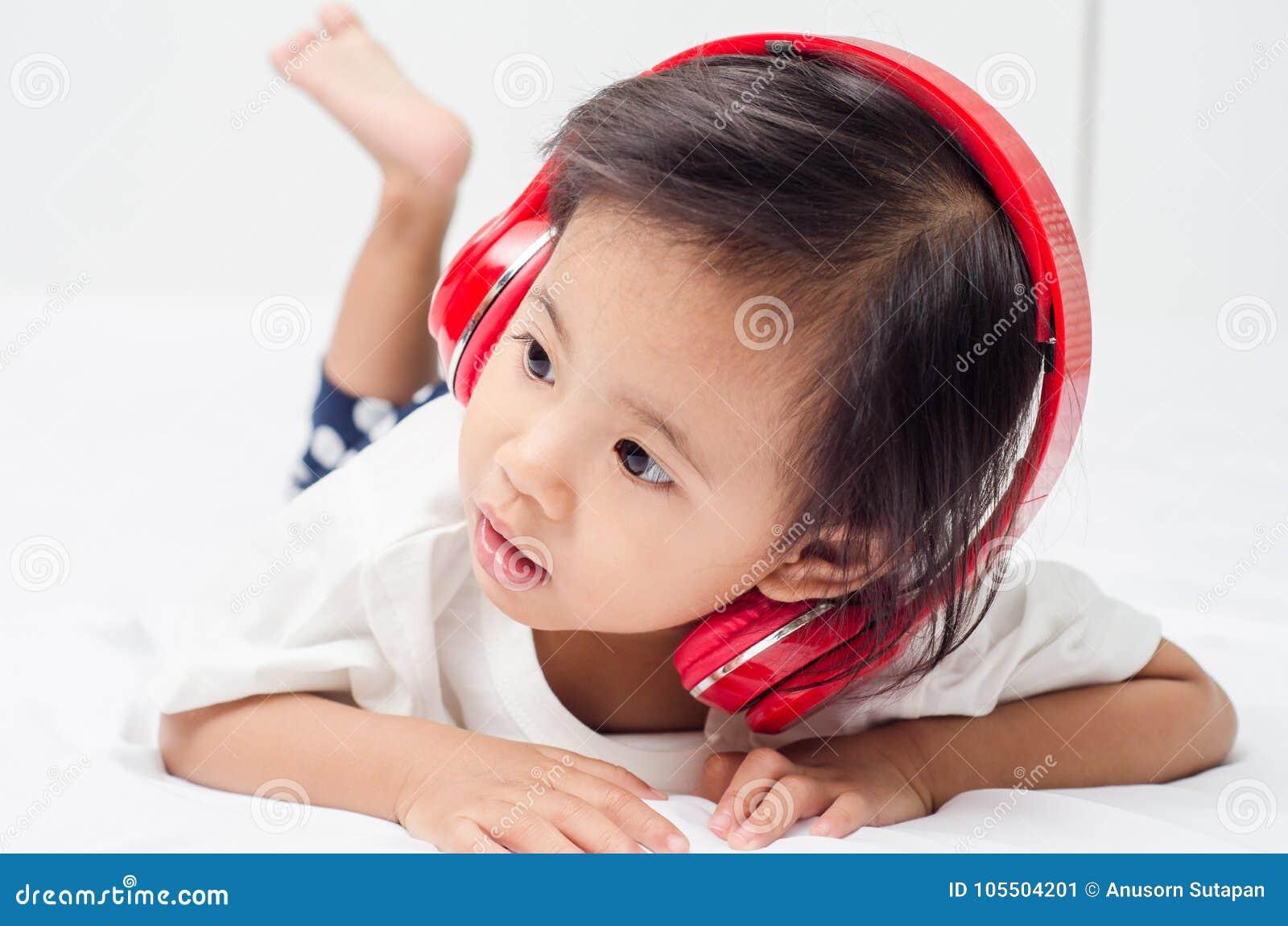 Ασιατικό μικρό κορίτσι με τα ακουστικά που βρίσκονται στο κρεβάτι στο σπίτι