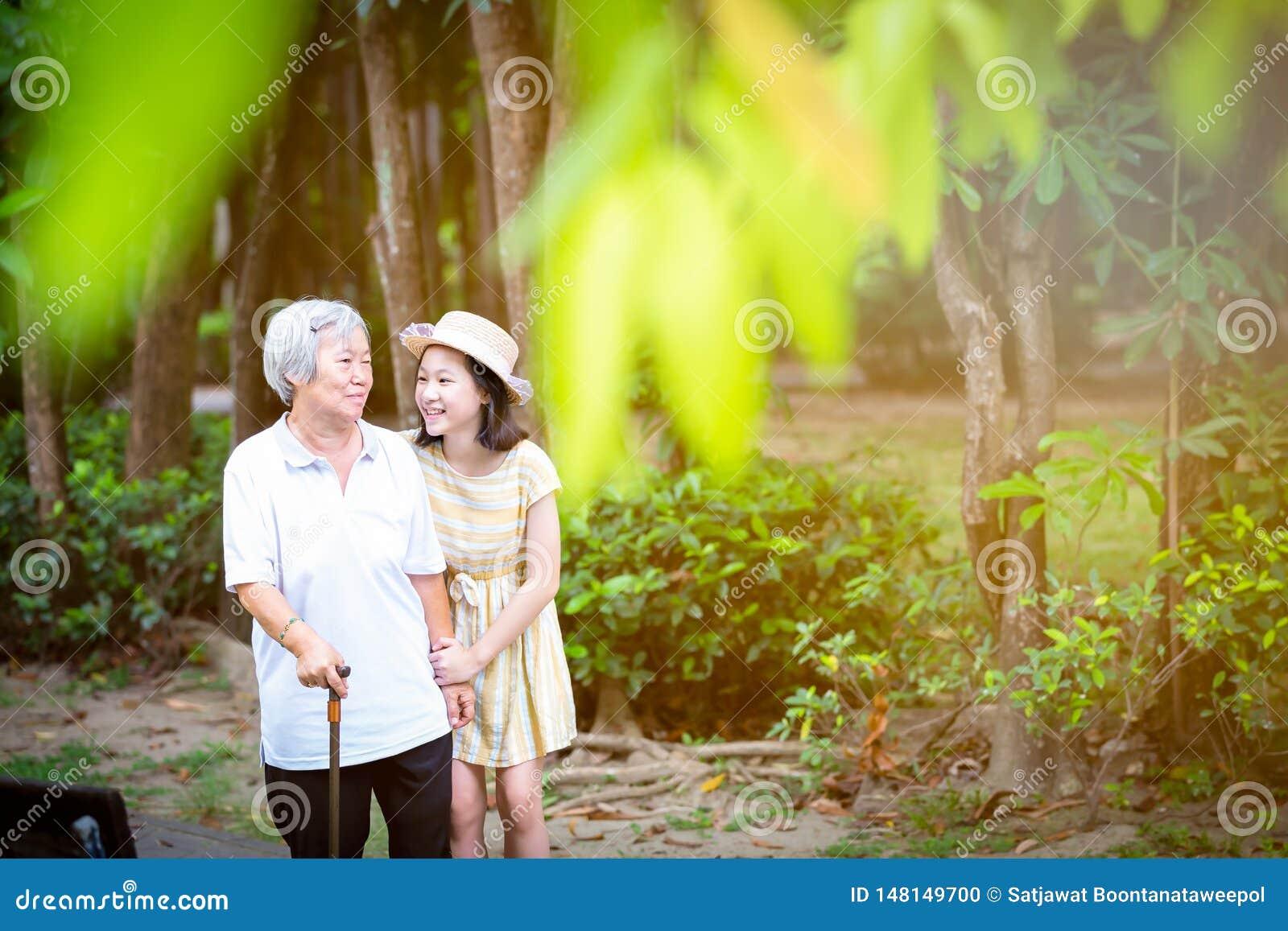 Ασιατικό μικρό κορίτσι που υποστηρίζει την ανώτερη γυναίκα με το ραβδί περπατήματος, την ευτυχείς χαμογελώντας γιαγιά και την εγγ