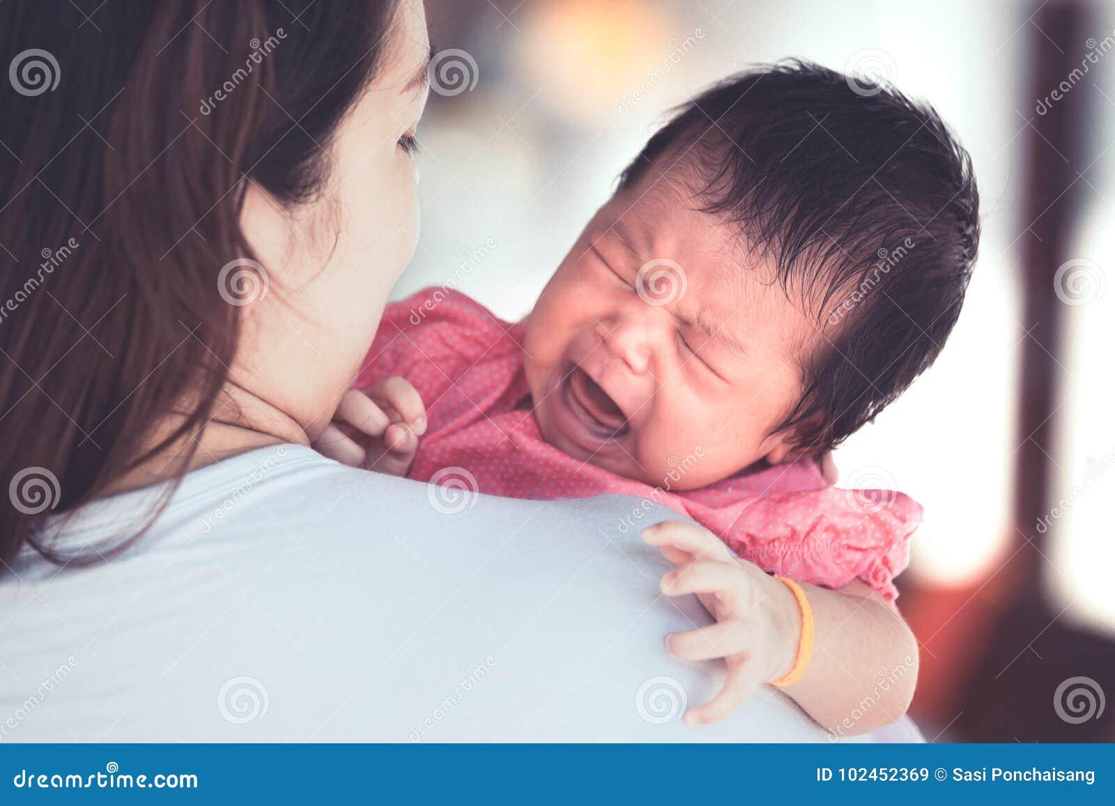Ασιατικό νεογέννητο κοριτσάκι που φωνάζει με προσπαθημένος στον ώμο μητέρων ` s