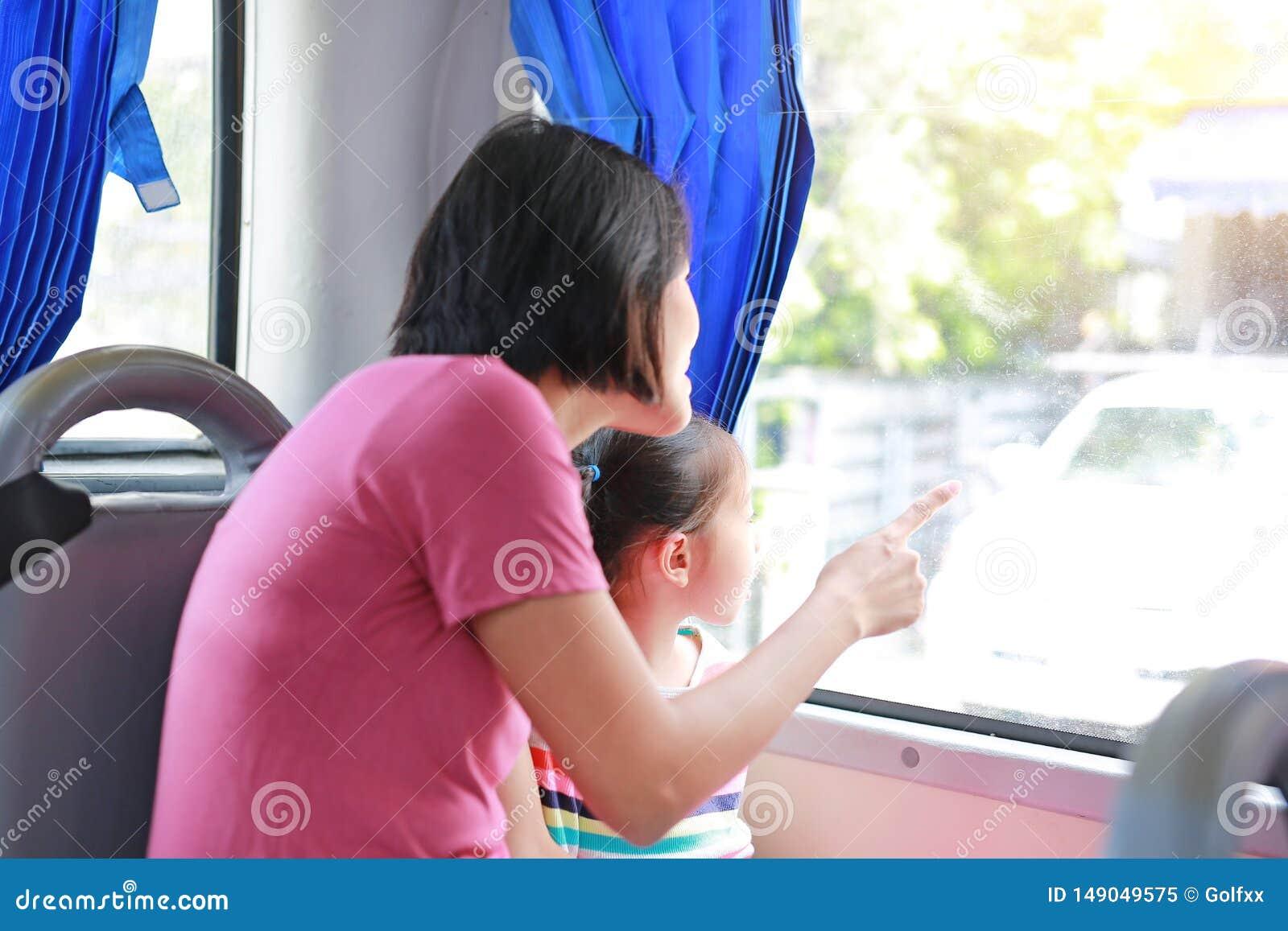 Ασιατικό mom και η συνεδρίαση κορών της στο λεωφορείο δημόσιων συγκοινωνιών Mom που δείχνει κάτι το κοίταγμα κοριτσιών παιδιών