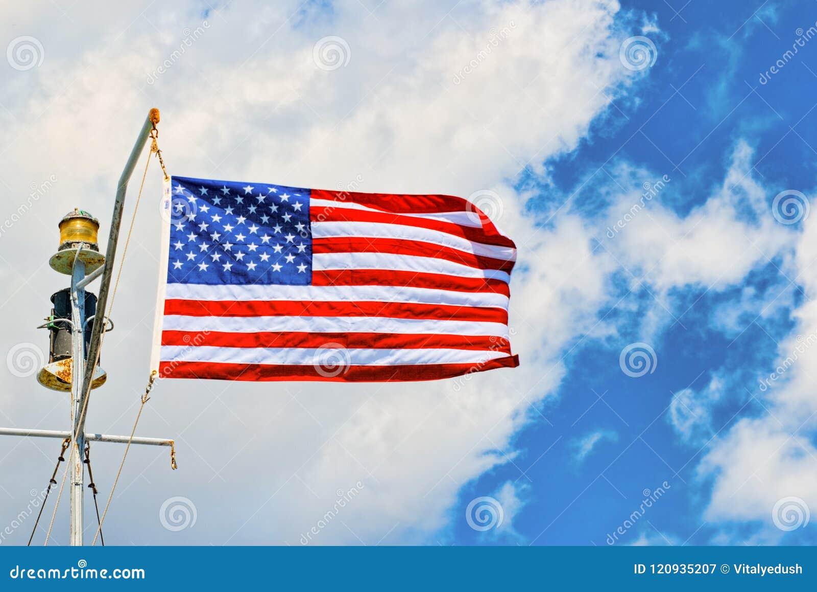Αστέρι-ριγωτοί κυματισμοί αμερικανικών σημαιών υπερήφανα ενάντια στο μπλε ουρανό