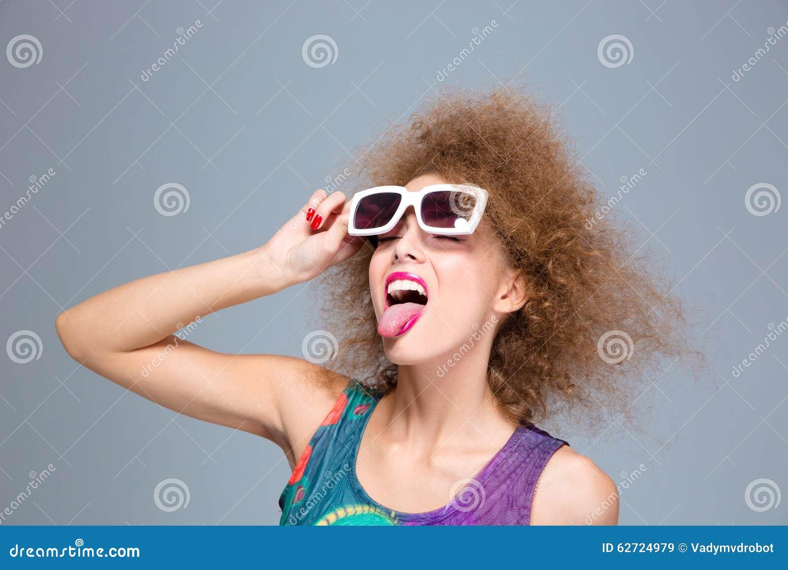 Αστεία σγουρή γυναίκα στα γυαλιά ηλίου με τις προσοχές ιδιαίτερες παρουσίαση γλώσσας
