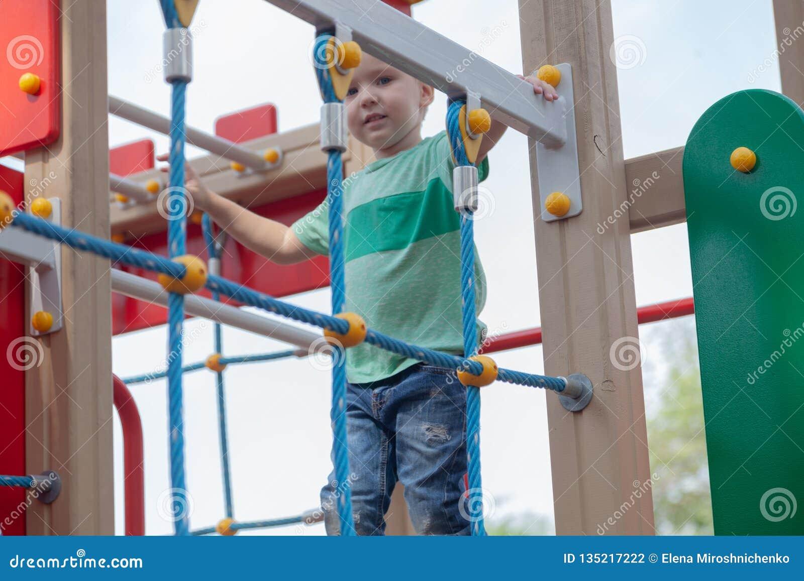 Αστεία χαριτωμένα ξανθά παιχνίδια αγοράκι στην παιδική χαρά Η συγκίνηση της ευτυχίας, διασκέδαση, χαρά