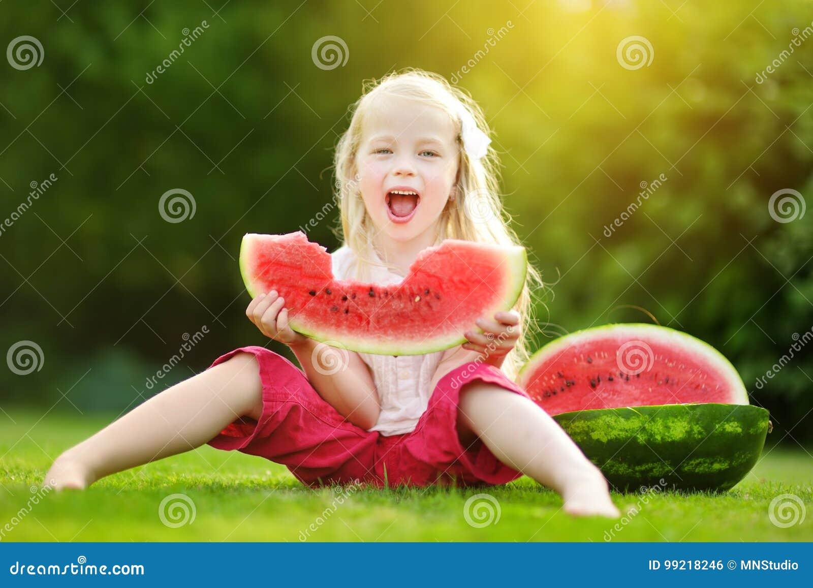 Αστείο μικρό κορίτσι που δαγκώνει μια φέτα του καρπουζιού υπαίθρια τη θερμή και ηλιόλουστη θερινή ημέρα