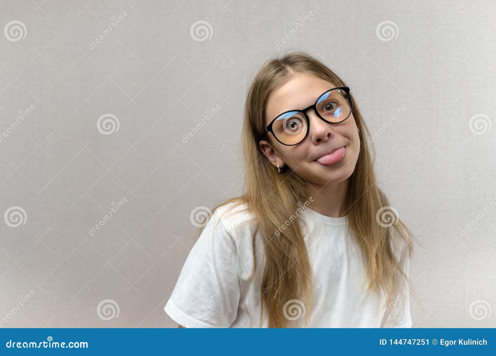 Αστείο ξανθό κορίτσι στα γυαλιά που το πρόσωπό της, μιμούμενος, έχοντας τη διασκέδαση E