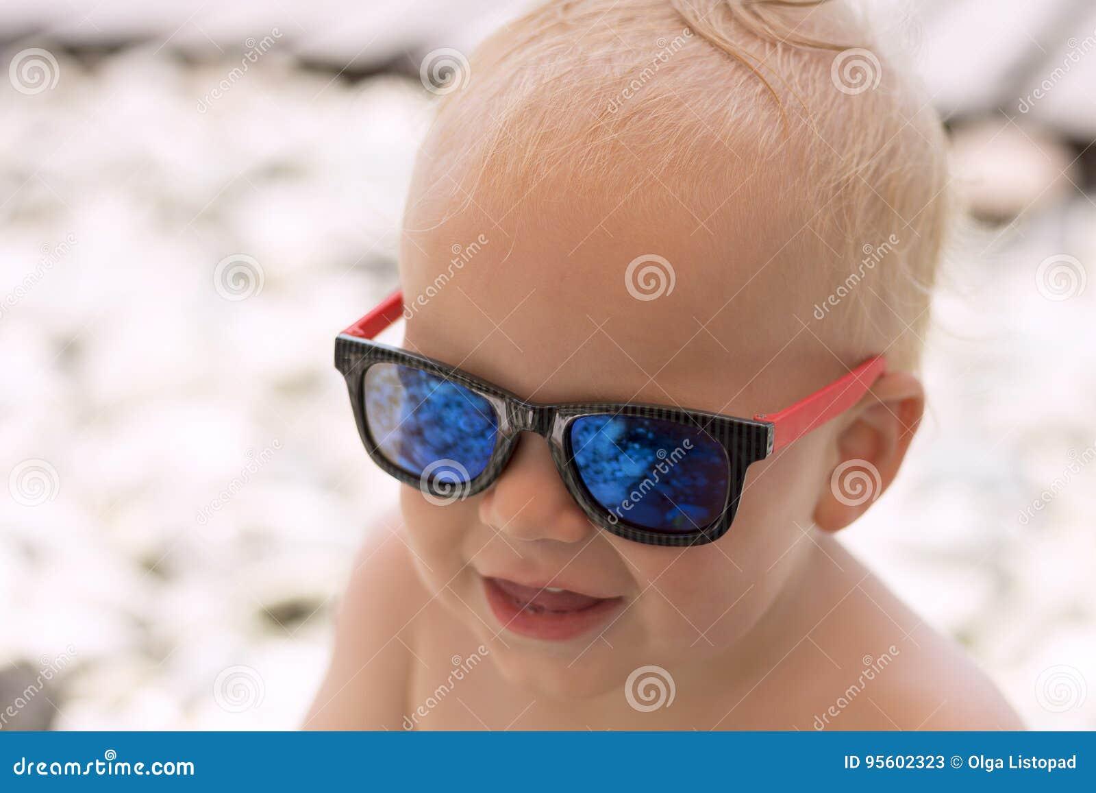 f4e0320d17 Αστείο χαμογελώντας αγοράκι στα γυαλιά ηλίου στην παραλία Οι πέτρες  απεικονίζονται στα γυαλιά Λίγος προϊστάμενος στις
