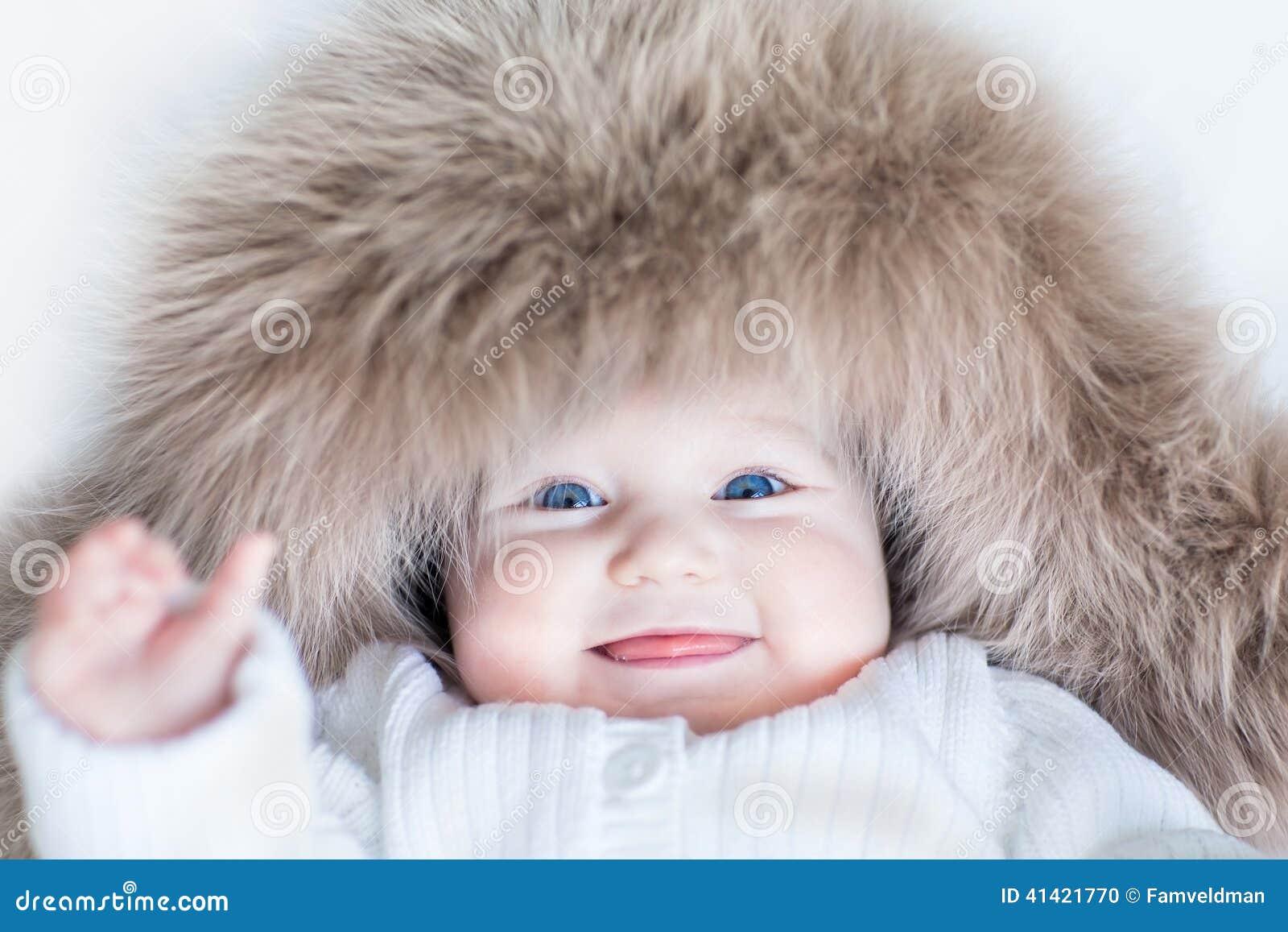 Αστείο χαριτωμένο κοριτσάκι που φορά το τεράστιο χειμερινό καπέλο