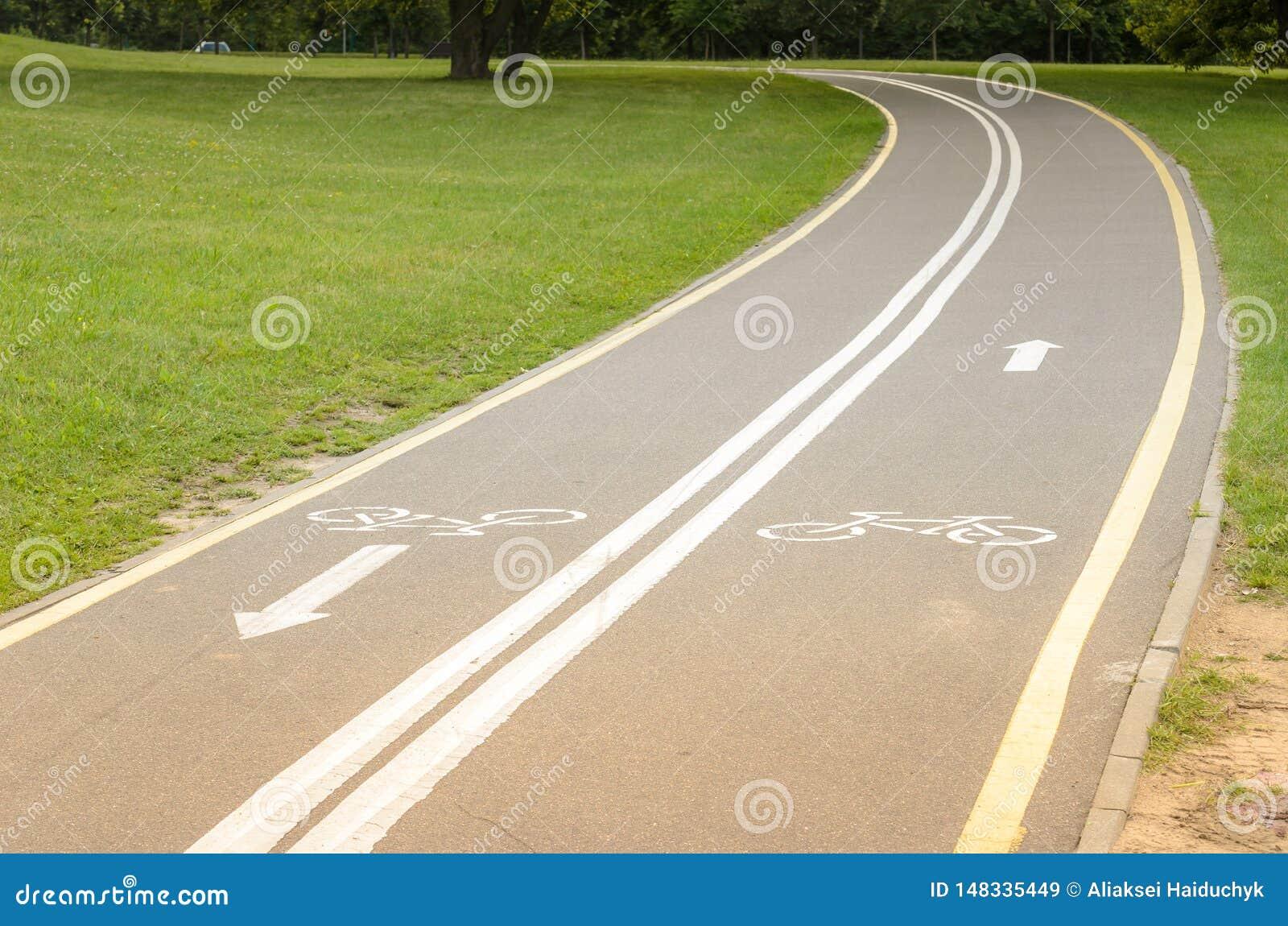 Ασφαλτωμένη διαδρομή ποδηλάτων στο πάρκο/ασφαλτωμένη διαδρομή ποδηλάτων στο πάρκο με μια πράσινη χλόη