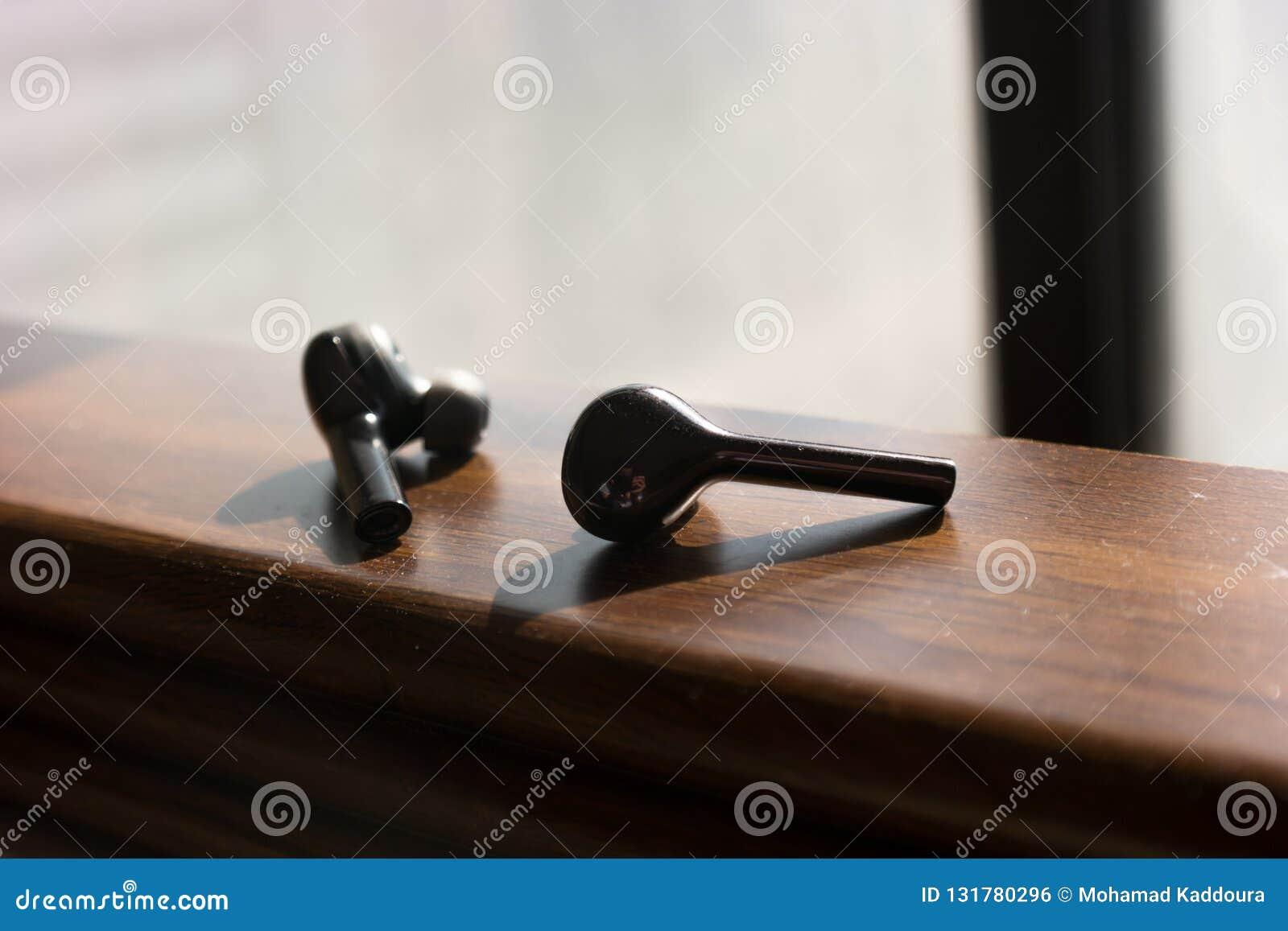 Ασύρματα μαύρα earbuds σε μια ξύλινη σύσταση