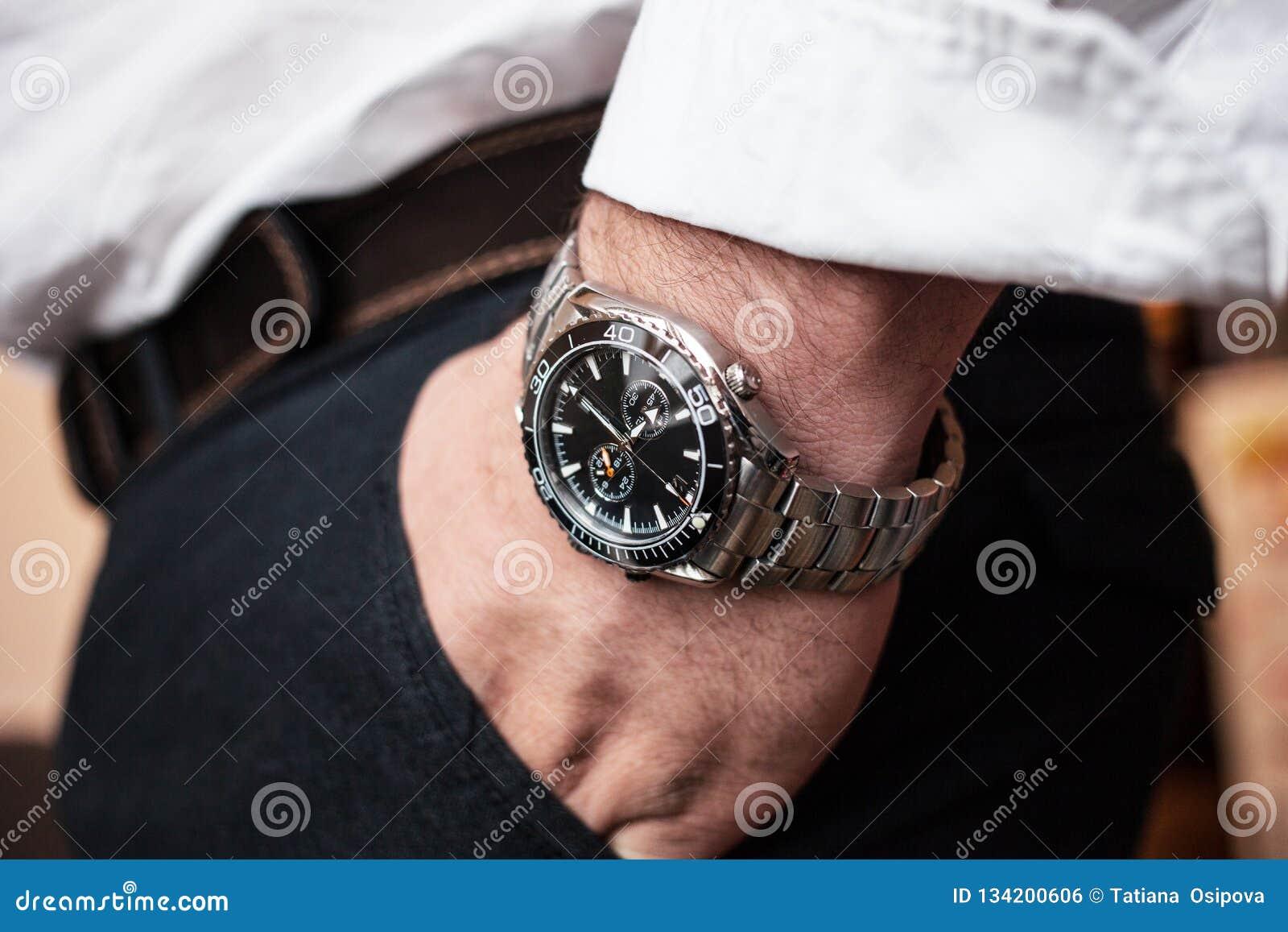 Ατόμων κινηματογραφήσεων σε πρώτο πλάνο wristwatch στο άσπρο πουκάμισο