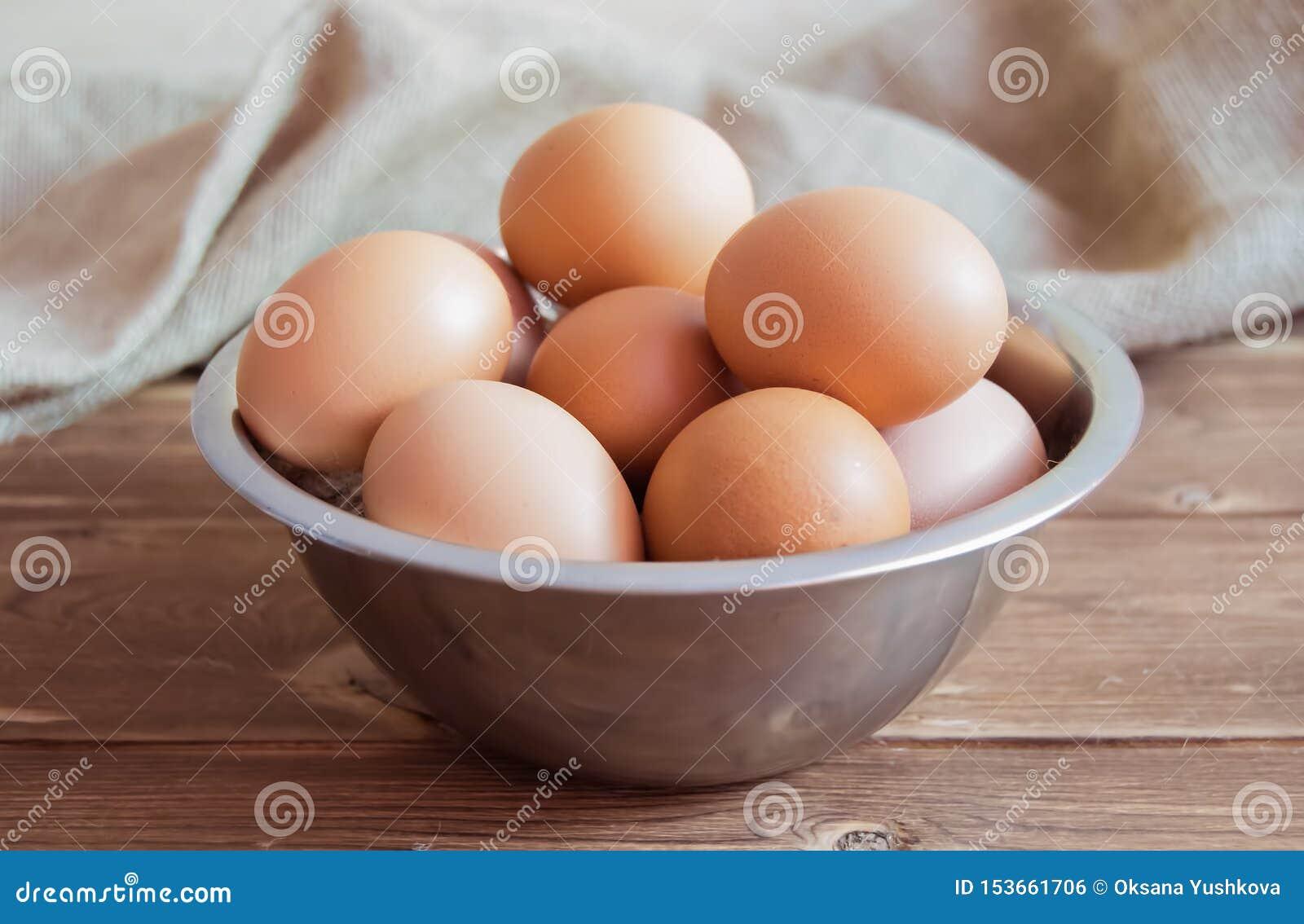 Αυγά κοτόπουλου σε ένα κύπελλο μετάλλων σε έναν ξύλινο πίνακα