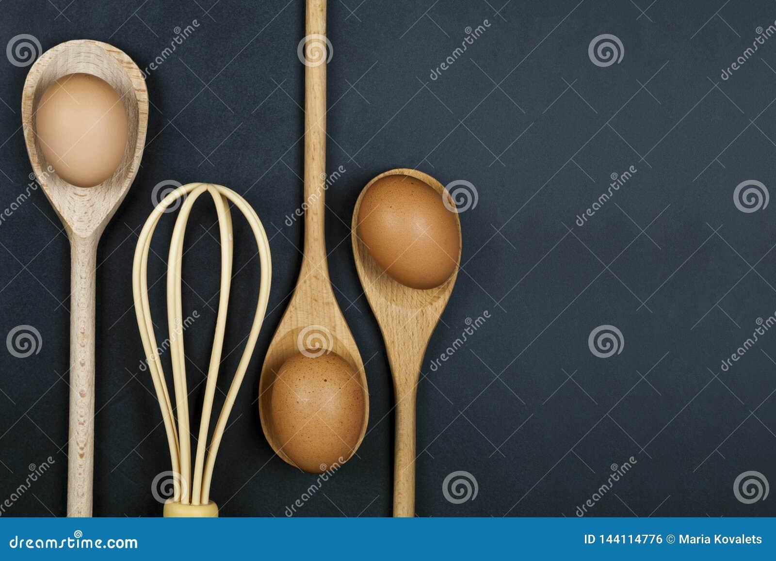 Αυγά, ξύλινα κουτάλι και μουστάκι Εργαλείο κουζινών για το κέικ, τη ζύμη ή τα μπισκότα στο υπόβαθρο ραχών