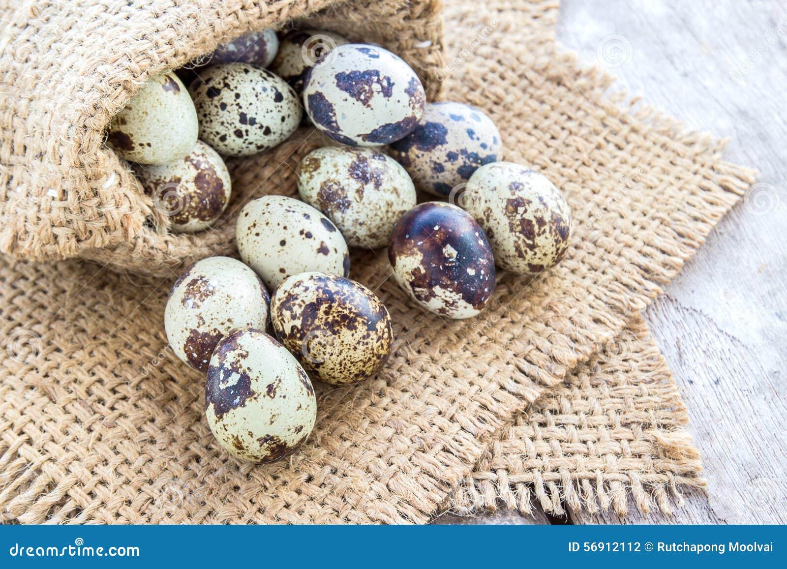 Αυγά ορτυκιών burlap στο σάκο σε έναν ξύλινο πίνακα
