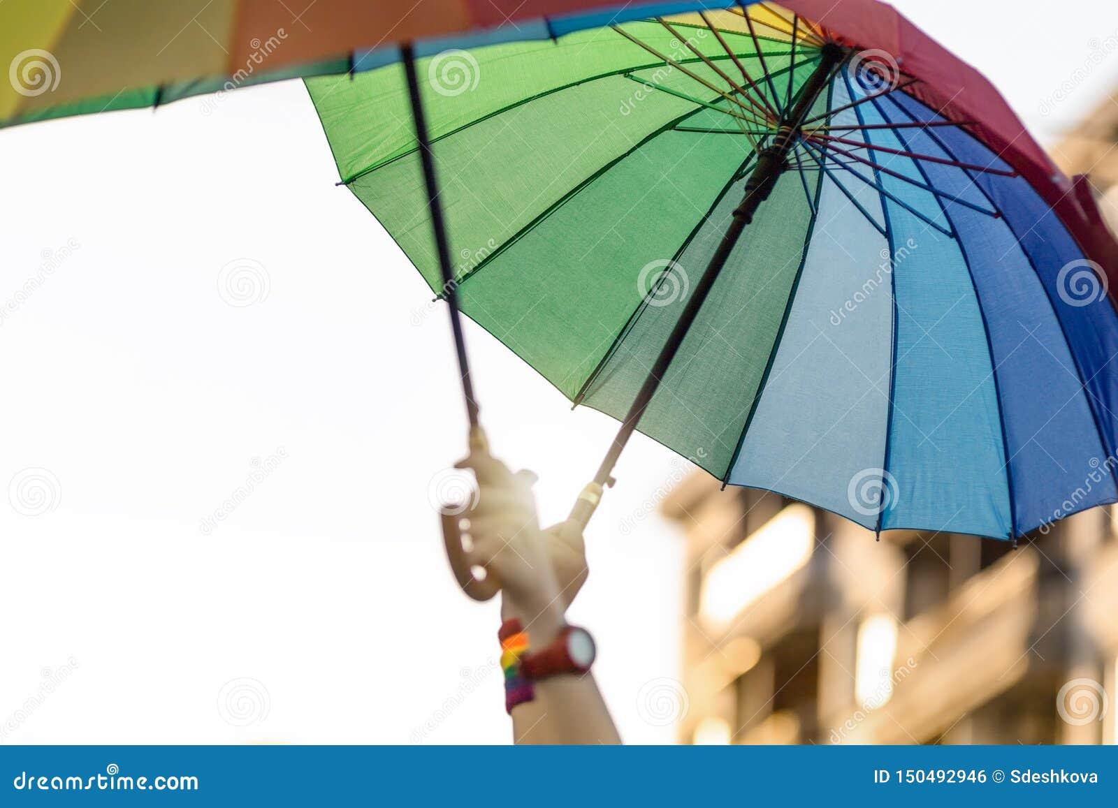 Αυξημένα χέρια με χρωματισμένες τις ουράνιο τόξο ομπρέλες