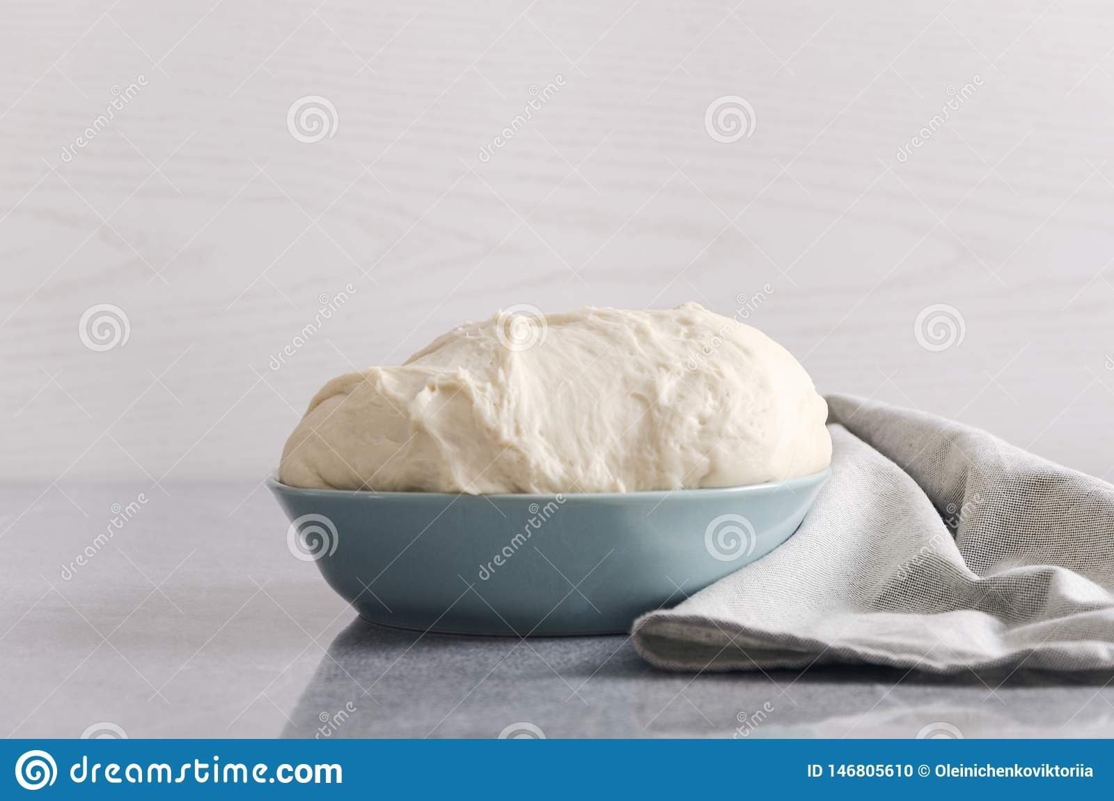Αυξημένη ακατέργαστη ζύμη για την πίτσα στο μπλε κύπελλο στον πίνακα κουζινών