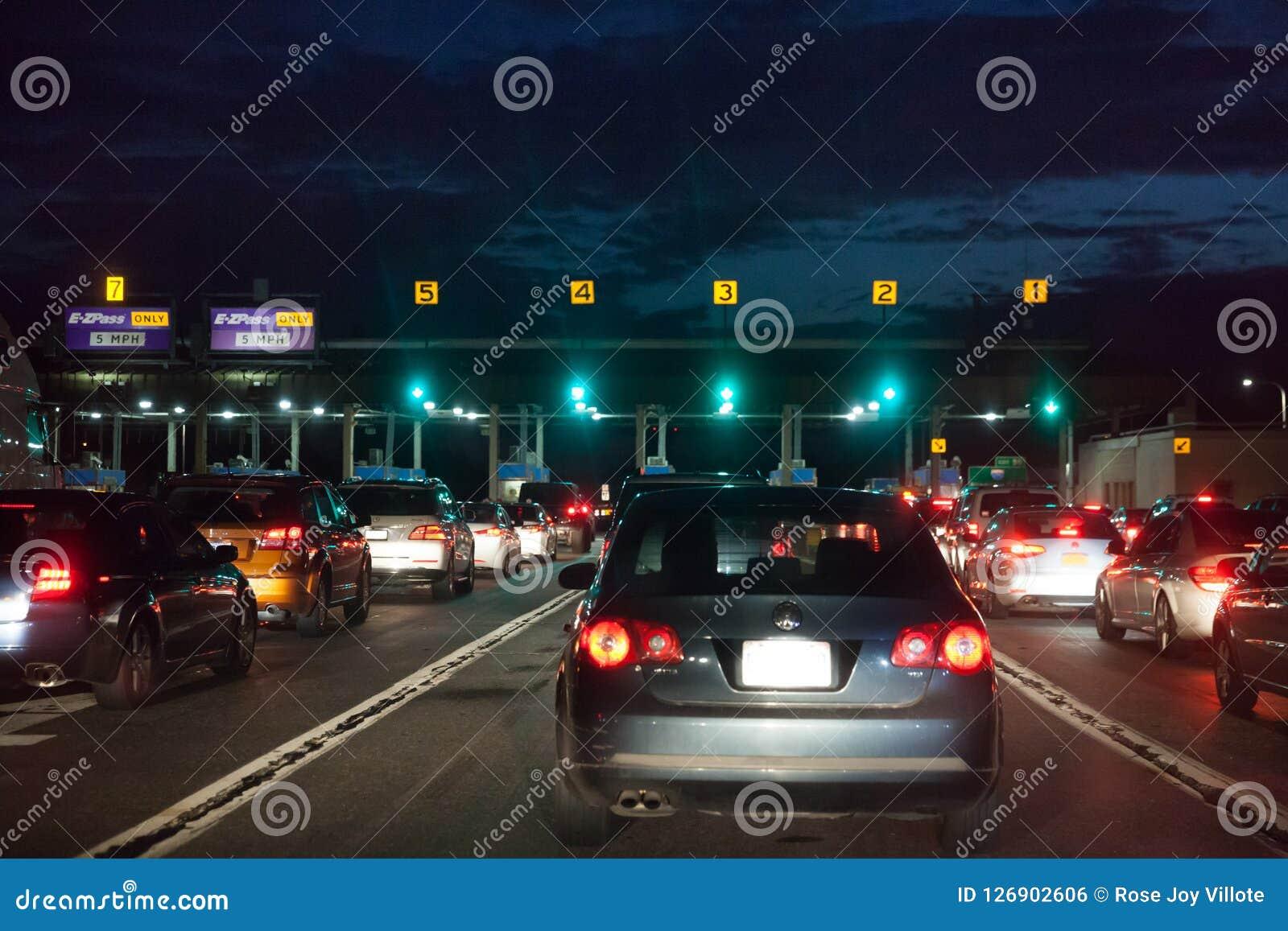 Αυτοκίνητα σε μια διάταξη τη νύχτα στην πύλη φόρου για να πληρώσει για την αμοιβή φόρου
