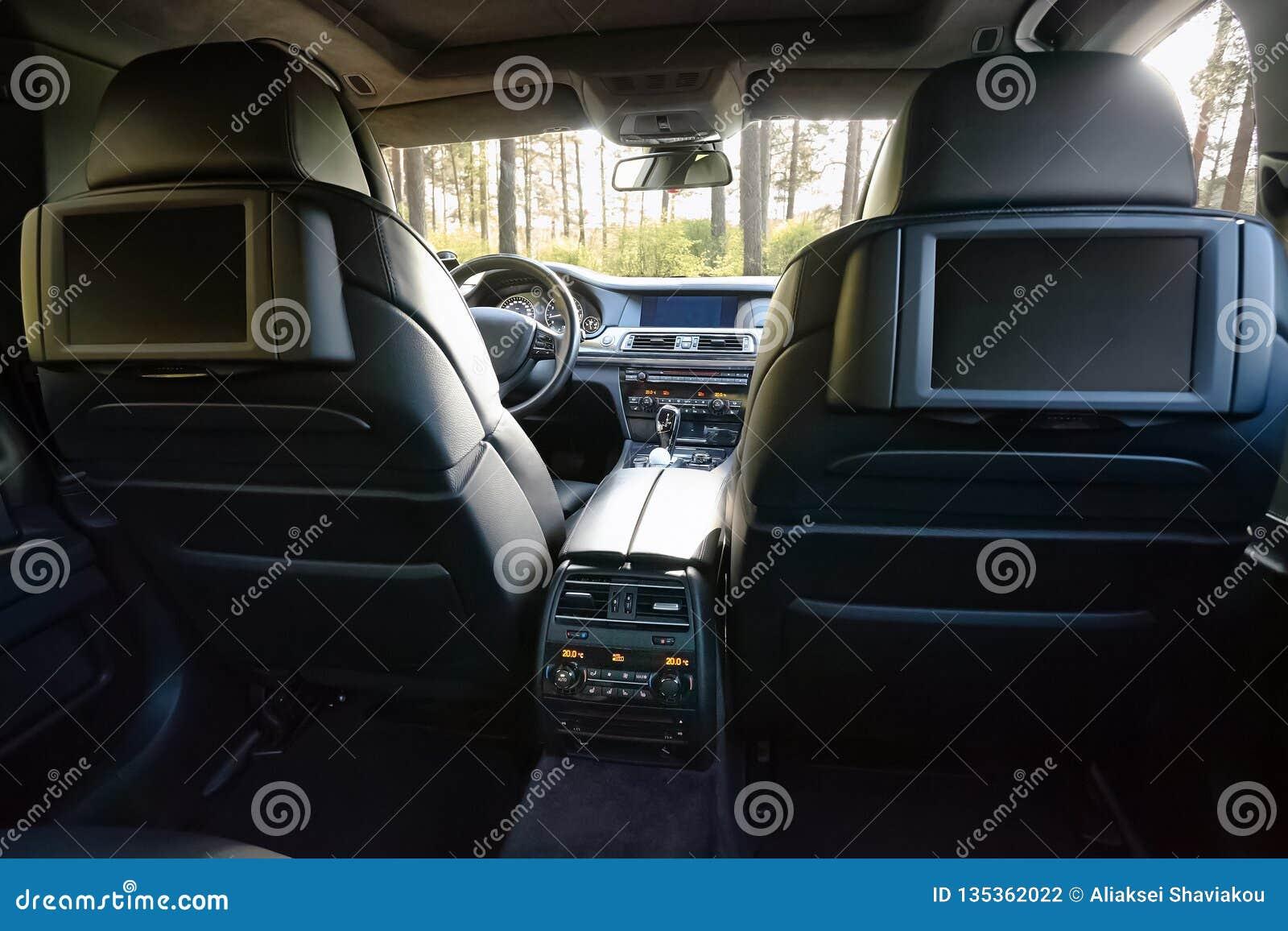αυτοκίνητο μέσα Εσωτερικό του σύγχρονου αυτοκινήτου πολυτέλειας γοήτρου Τρεις επιδείξεις TV για τον επιβάτη με το διάστημα και τη