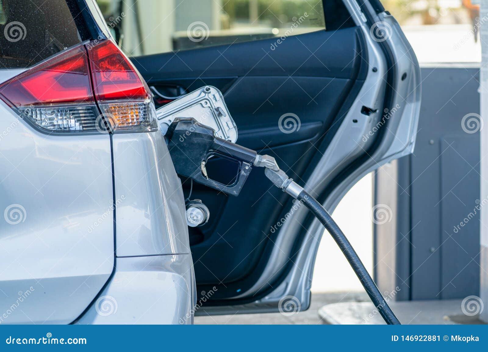Αυτοκίνητο που γεμίζει επάνω τη δεξαμενή αερίου σε ένα βενζινάδικο, με την πόρτα ανοικτή