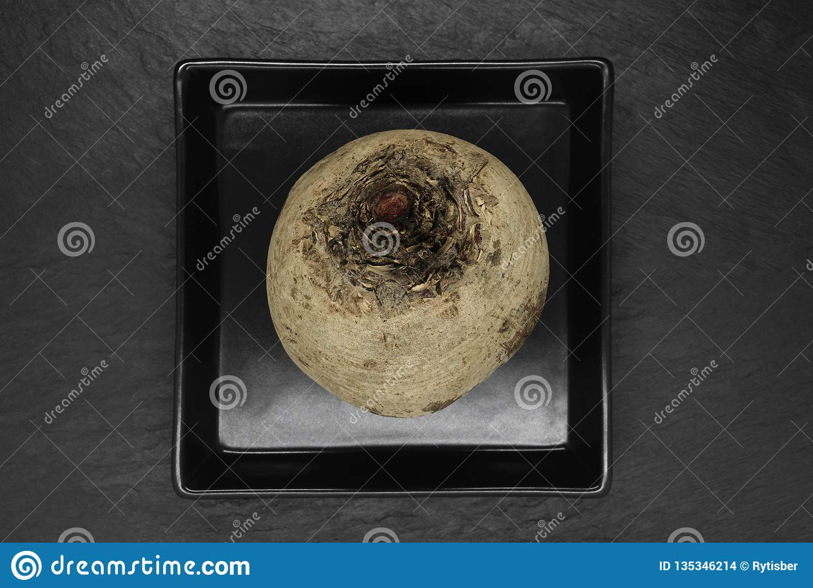 Αφηρημένη σύνθεση στρογγυλών ολόκληρων των παντζαριών που τοποθετούνται στο μαύρο πιάτο και το μαύρο υπόβαθρο πετρών