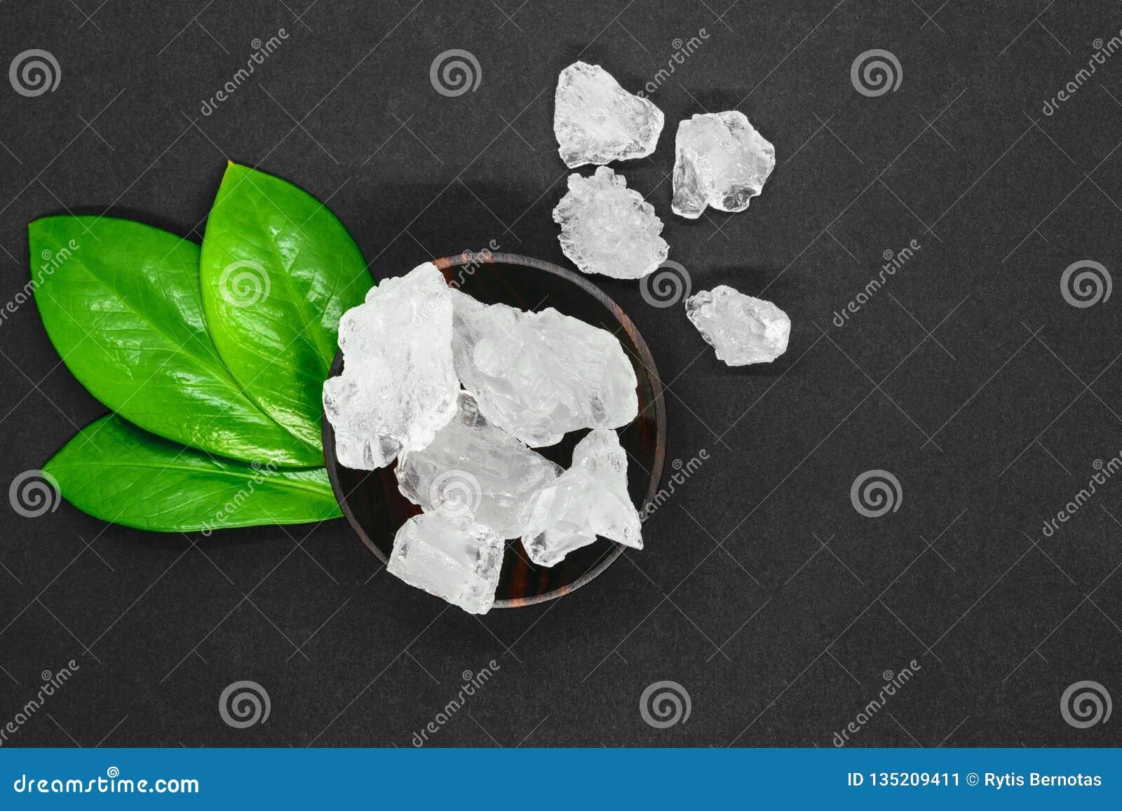 Αφηρημένη σύνθεση των πράσινων φύλλων, του ξύλινου σκοτεινού κύπελλου και των μεγάλων αλατισμένων κρυστάλλων ζάχαρης ή στο γκρίζο