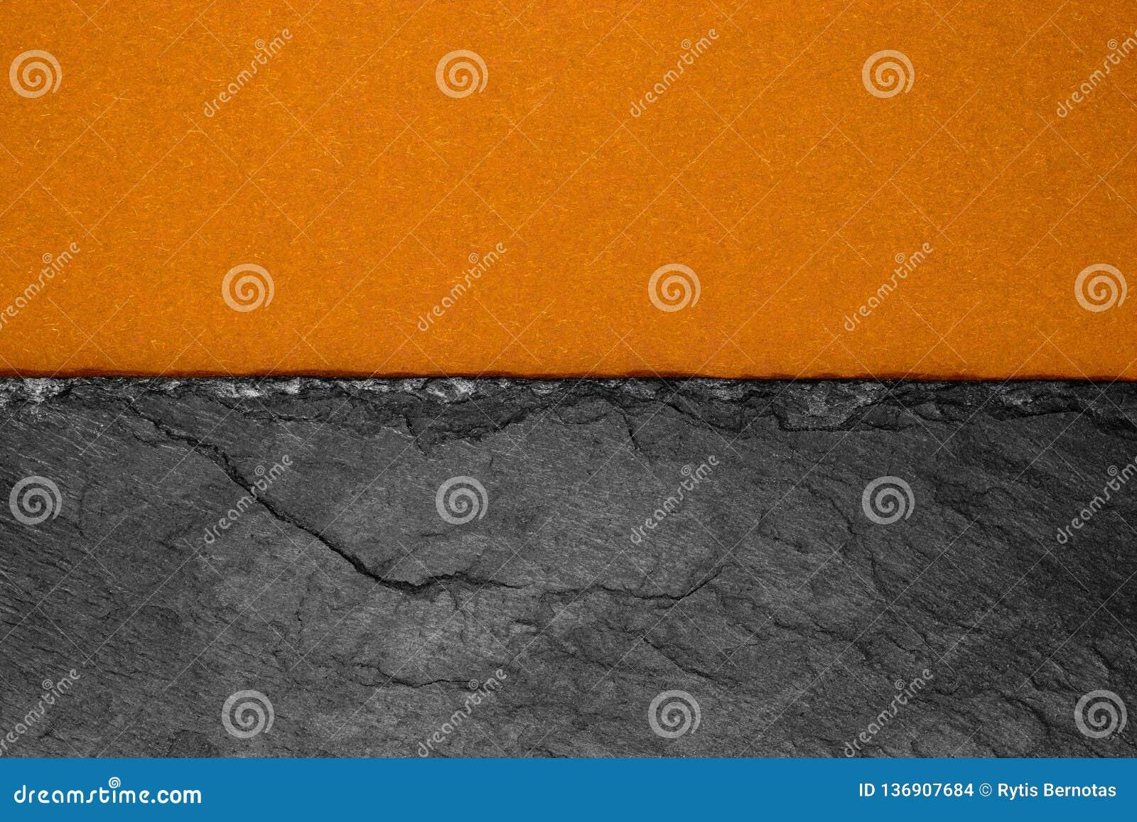 Αφηρημένη σύνθεση υποβάθρου διαιρεσμένος στο μισό ματ σκούρο παρτοκαλί έγγραφο χρώματος και τη μαύρη πέτρα με το διάστημα αντιγρά