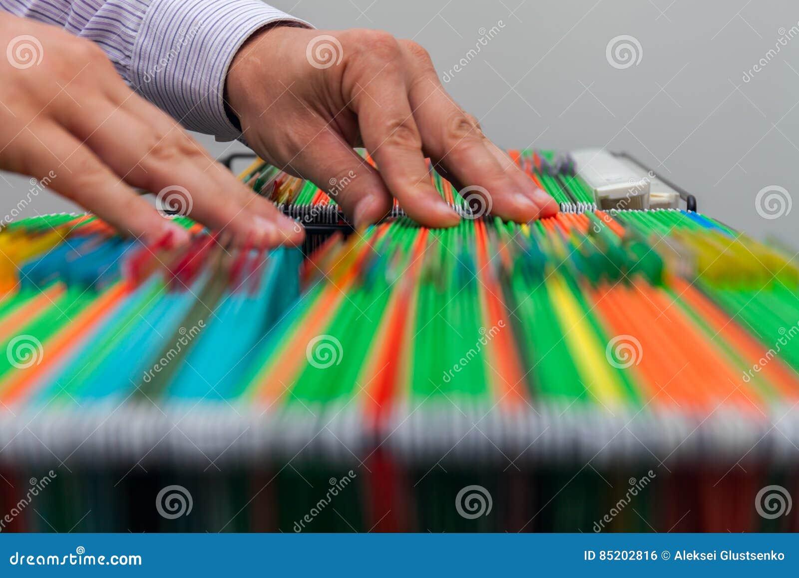Αφηρημένοι φάκελλοι αρχείων υποβάθρου ζωηρόχρωμοι κρεμώντας στο συρτάρι Αρσενικά χέρια που φαίνονται έγγραφο ολόκληρο σε έναν σωρ