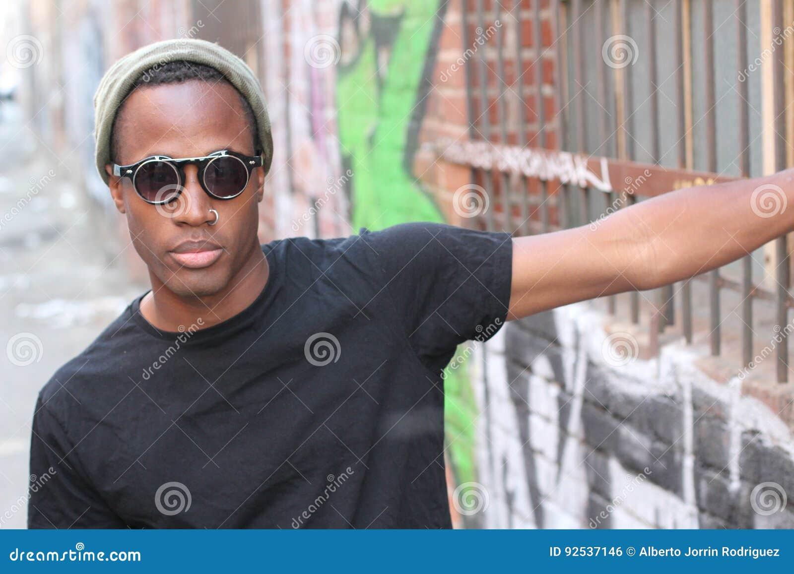 Αφρικανική φθορά ατόμων μόδας γυαλιά ηλίου, beanie, διαπεραστικό και μαύρο γράμμα Τ πέρα από το αστικό υπόβαθρο στην αλέα πόλεων
