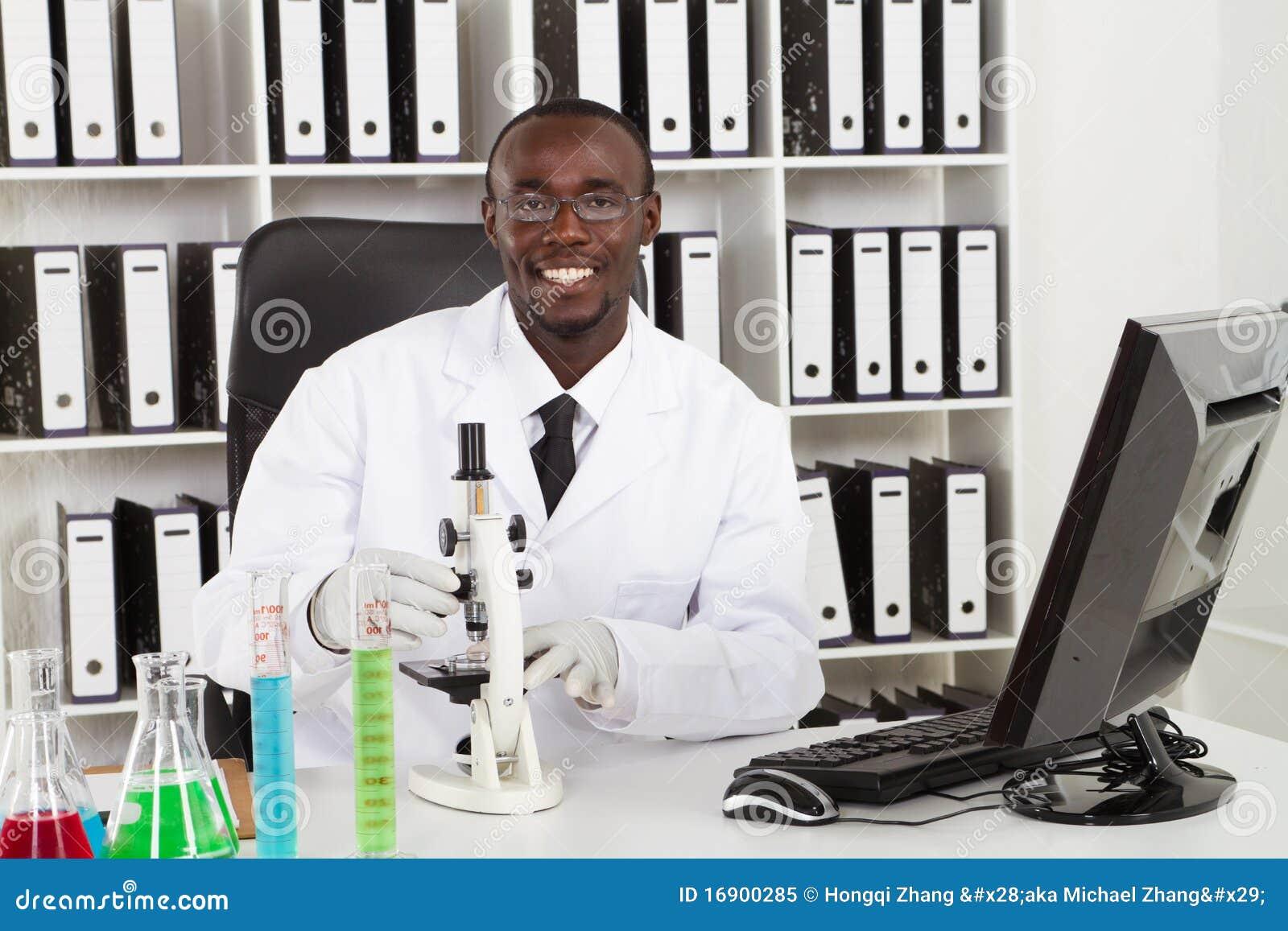 27b8f18829 Ιατρικός επιστήμονας αφροαμερικάνων που φορά το παλτό εργαστηρίων με τους  σωλήνες μικροσκοπίων και δοκιμής στο εργαστήριο. Φωτογραφία ...