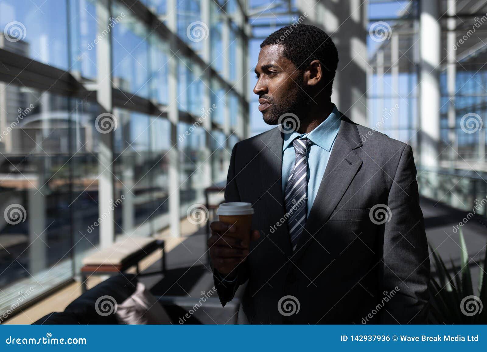 Αφροαμερικάνος του επιχειρηματία με το φλυτζάνι καφέ που φαίνεται μακριά στην αρχή