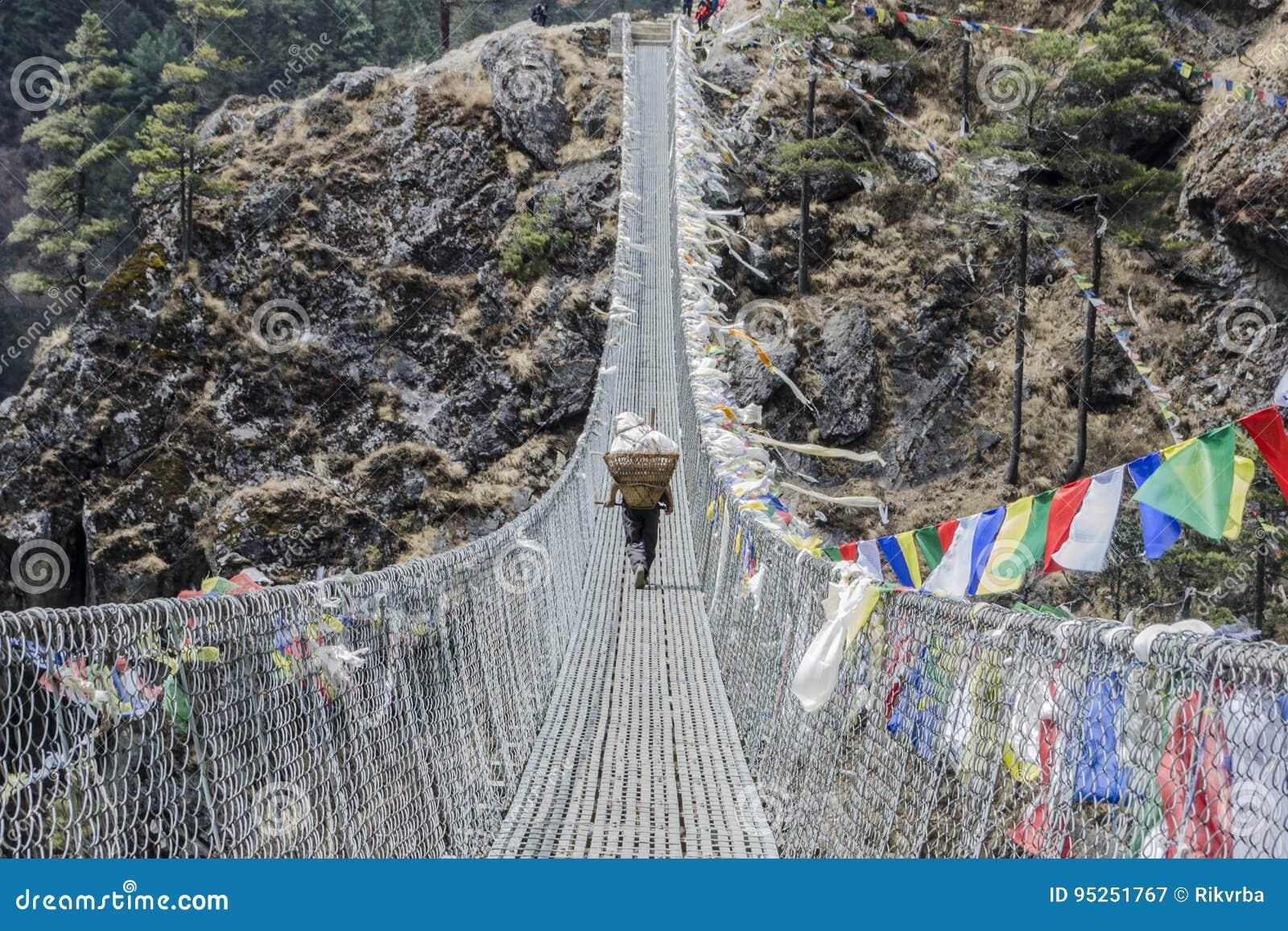 Αχθοφόρος sherpa Himalayan στη γέφυρα σχοινιών