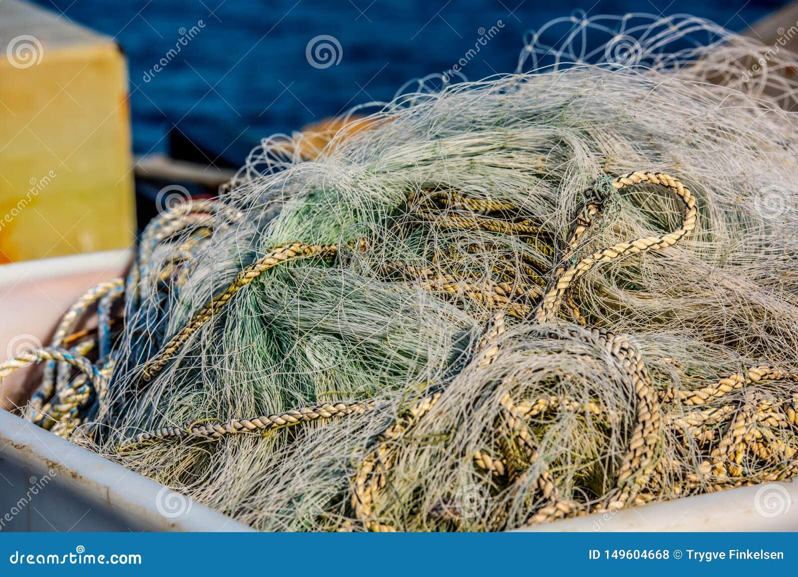 Αχρησιμοποίητα πράσινα δίχτυα του ψαρέματος σε έναν σωρό
