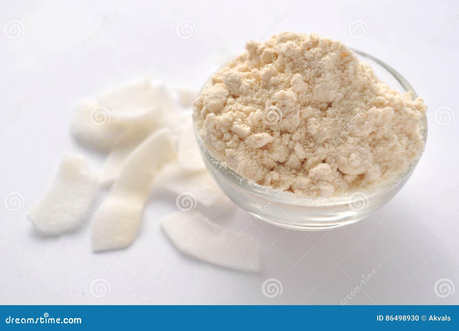 Αλεύρι και νιφάδες καρύδων στο άσπρο υπόβαθρο Σκόνη κρέμας σε ένα κύπελλο γυαλιού Απομονωμένος στο λευκό Εναλλακτικό γλουτένη-ελε